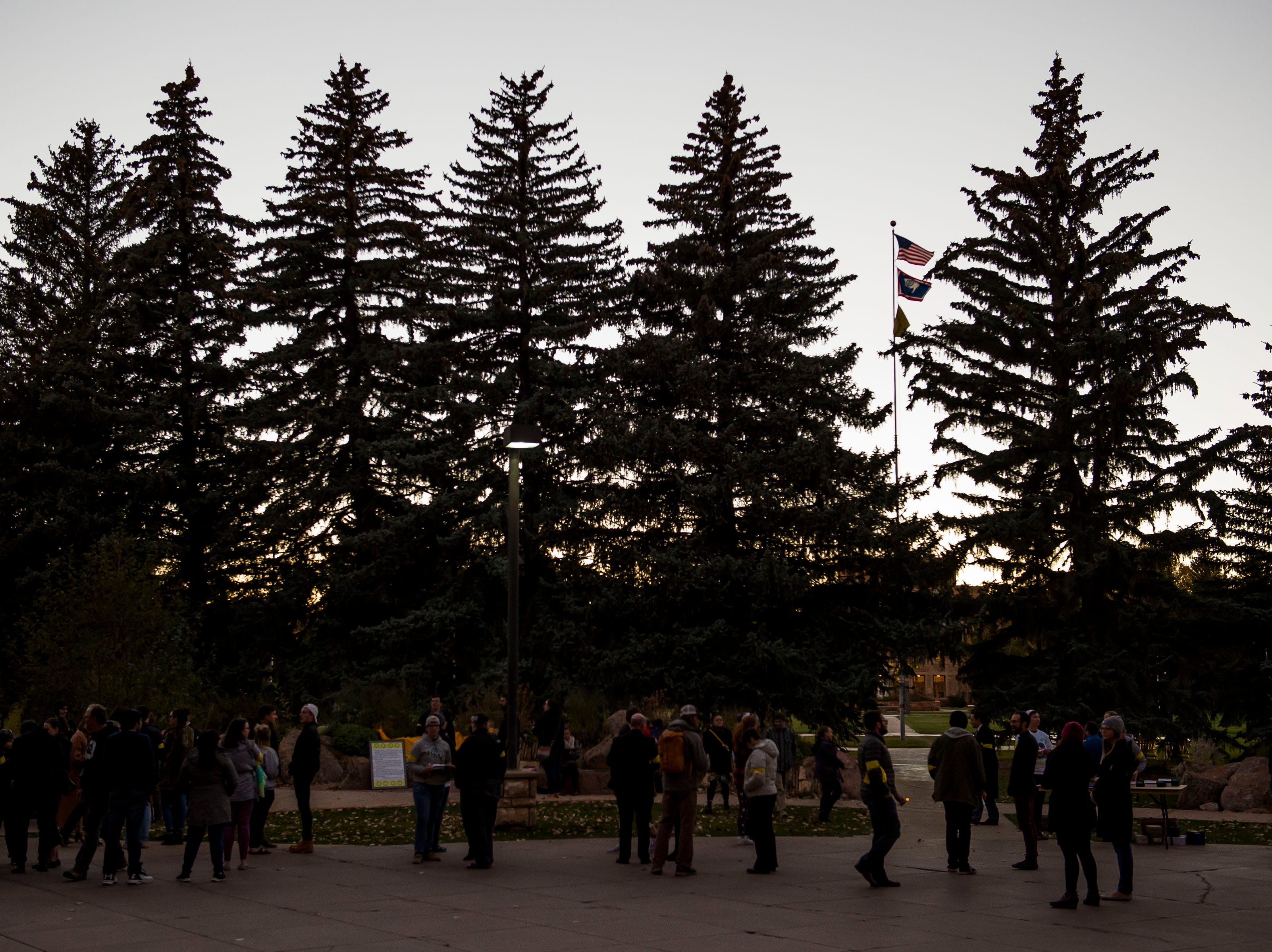 Vigil participants begin to gather before a candlelight vigil on the 20th anniversary of Matthew Shepard's death on Friday, Oct. 12, 2018, at Prexy's Pasture on the University of Wyoming campus in Laramie, Wyo.