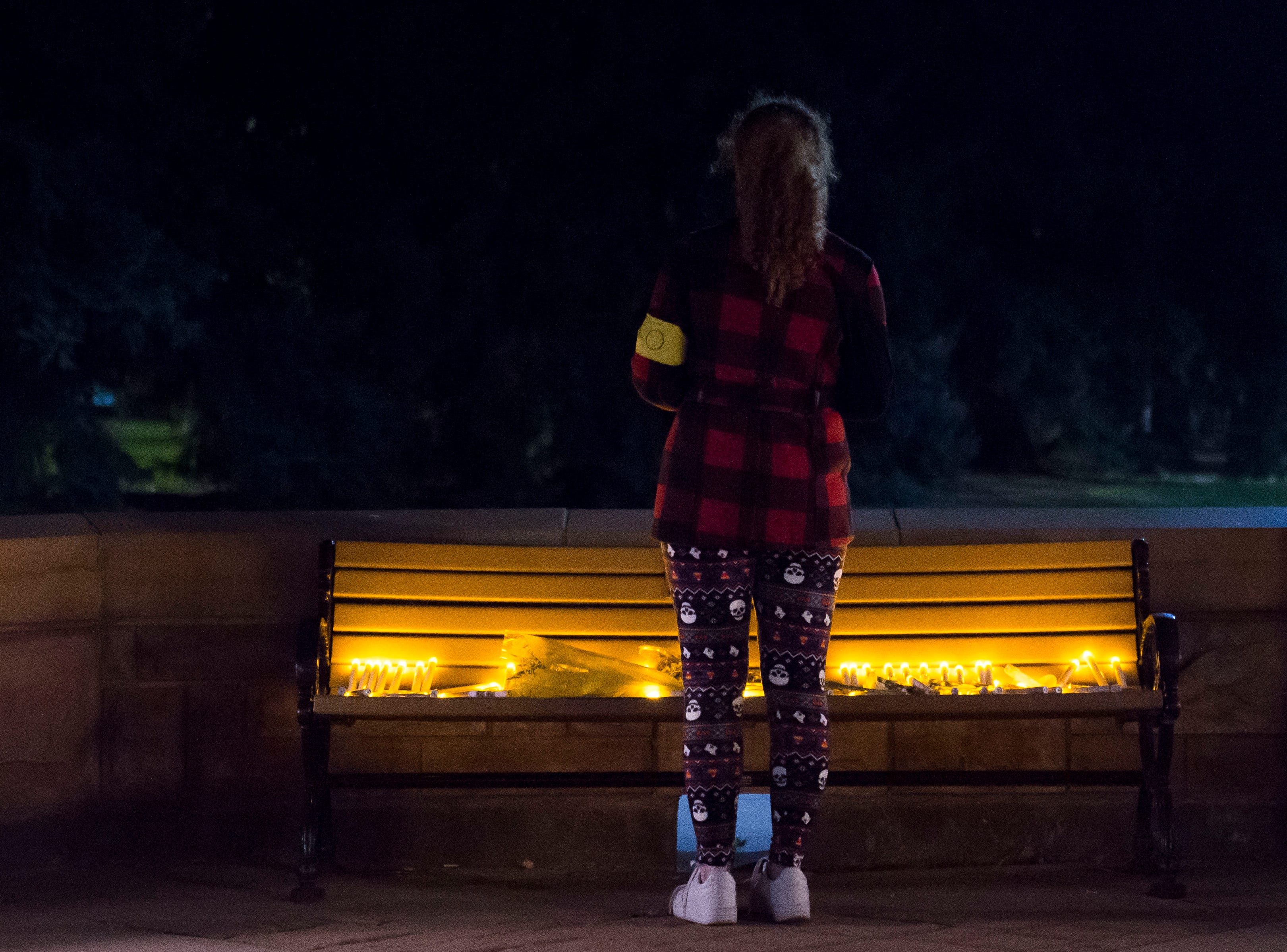 University of Wyoming junior journalism major Monica Olson pauses in front of a bench dedicated to Matthew Shepard after a candlelight vigil on the 20th anniversary of Shepard's death on Friday, Oct. 12, 2018, at Prexy's Pasture on the University of Wyoming campus in Laramie, Wyo.