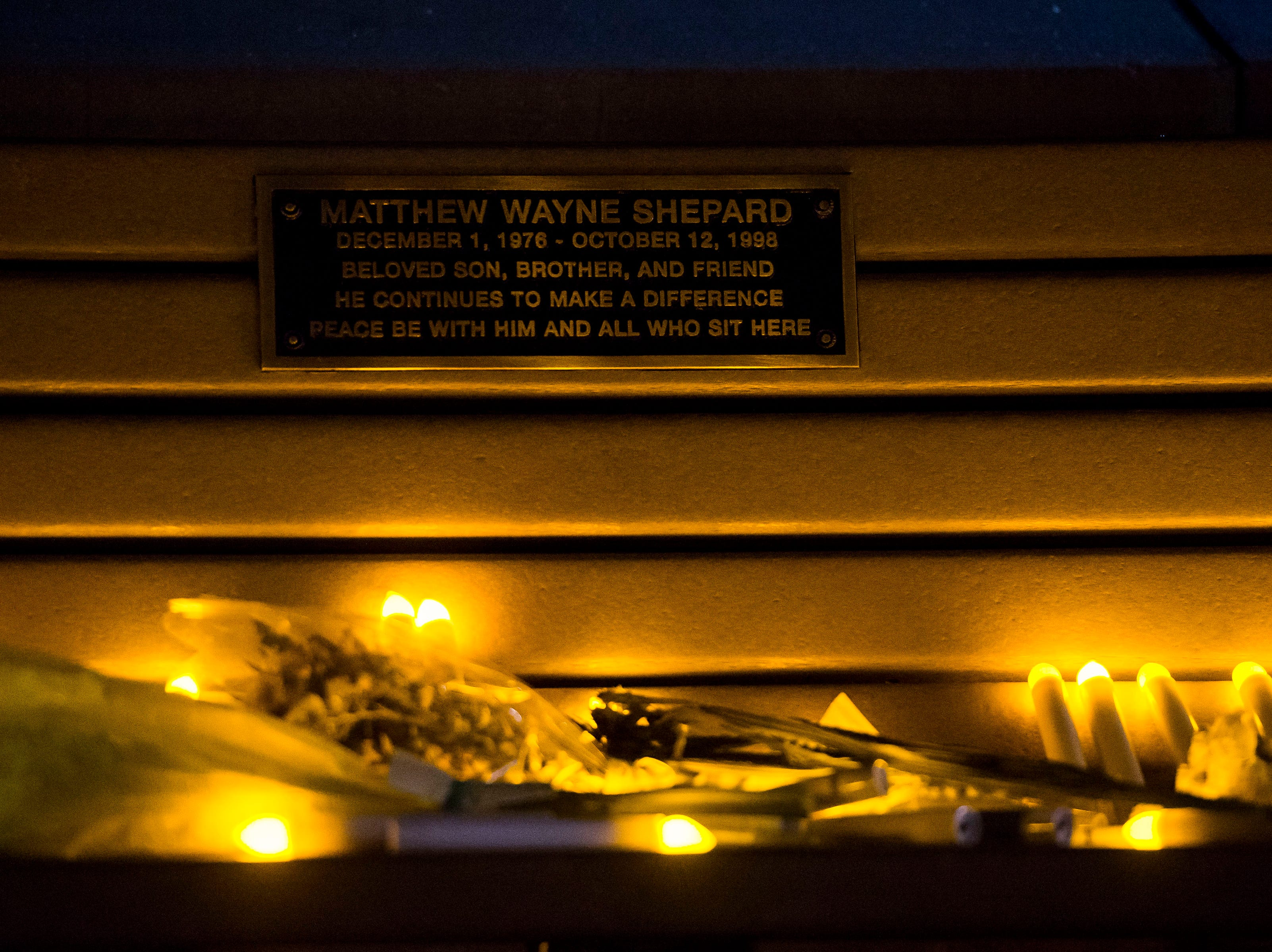 Vigil participants leave their flameless candles on the bench dedicated to Matthew Shepard after a vigil to in remembrance of the 20th anniversary of his death on Friday, Oct. 12, 2018, at Prexy's Pasture on the University of Wyoming campus in Laramie, Wyo.