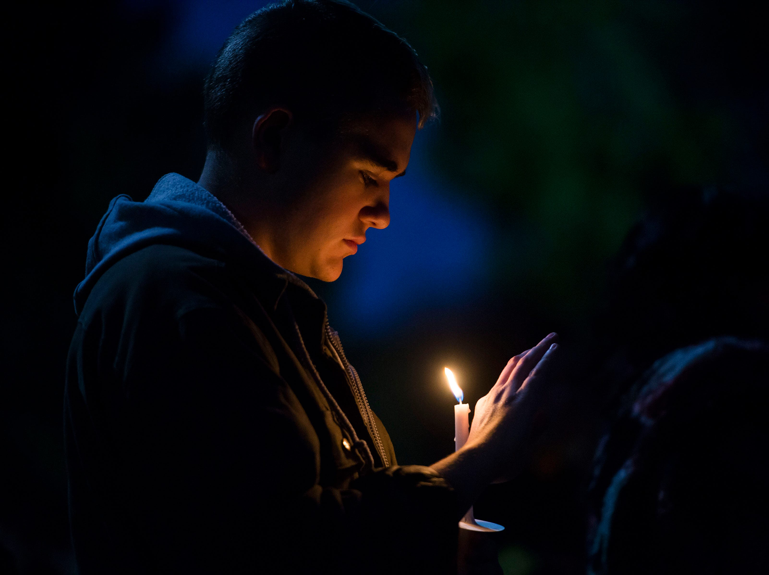 Lee Gauntlett holds a candle during a candlelight vigil on the 20th anniversary of Matthew Shepard's death on Friday, Oct. 12, 2018, at Prexy's Pasture on the University of Wyoming campus in Laramie, Wyo.