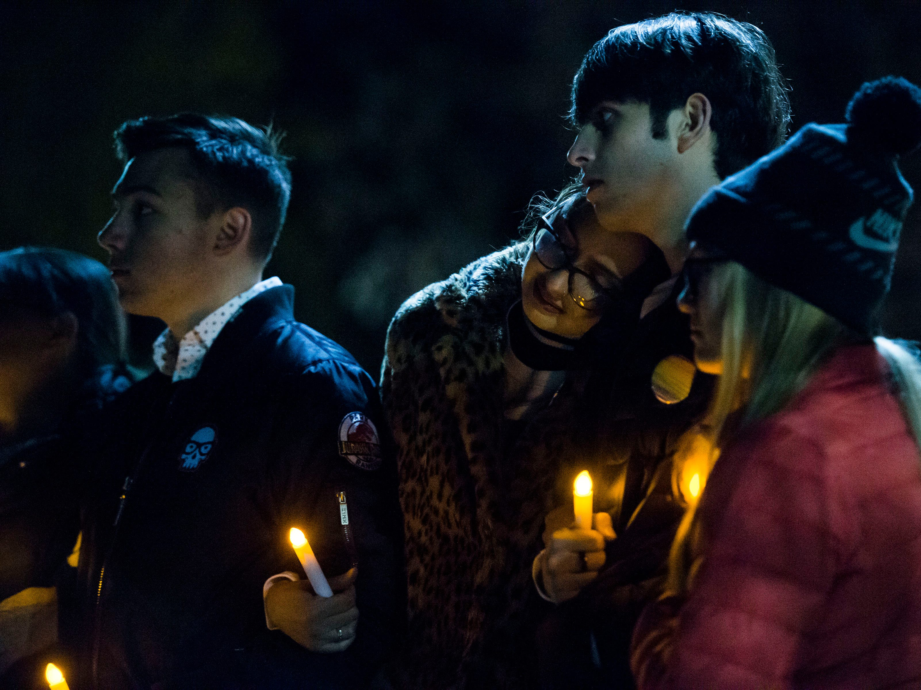 University of Wyoming sophomore Claire Olson rests her head of freshman Hayden Higgins' shoulder during a candlelight vigil on the 20th anniversary of Matthew Shepard's death on Friday, Oct. 12, 2018, at Prexy's Pasture on the University of Wyoming campus in Laramie, Wyo.