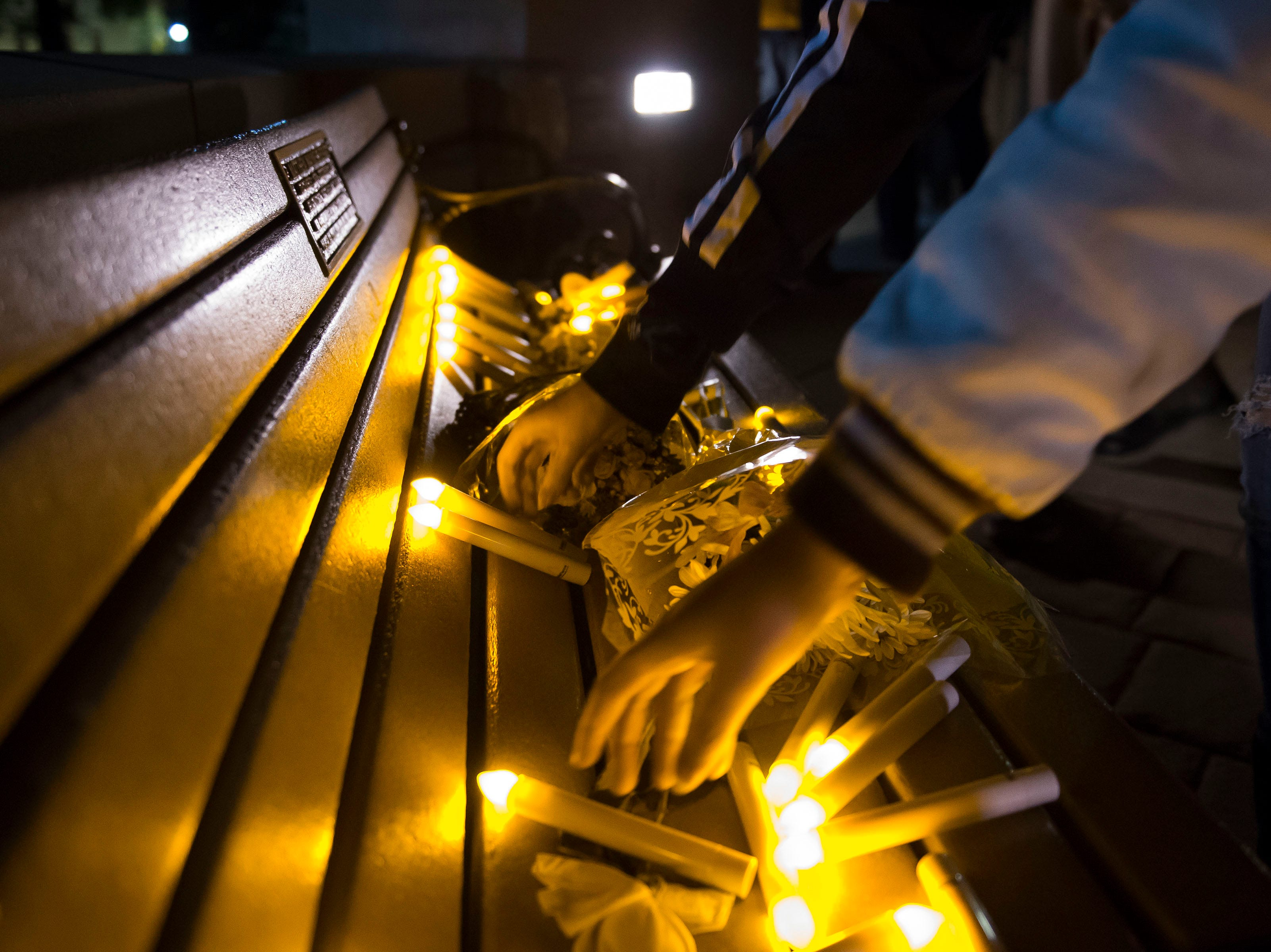 Vigil participants set their flameless candles down on a bench dedicated to Matthew Shepard after a candlelight vigil on the 20th anniversary of Shepard's death on Friday, Oct. 12, 2018, at Prexy's Pasture on the University of Wyoming campus in Laramie, Wyo.