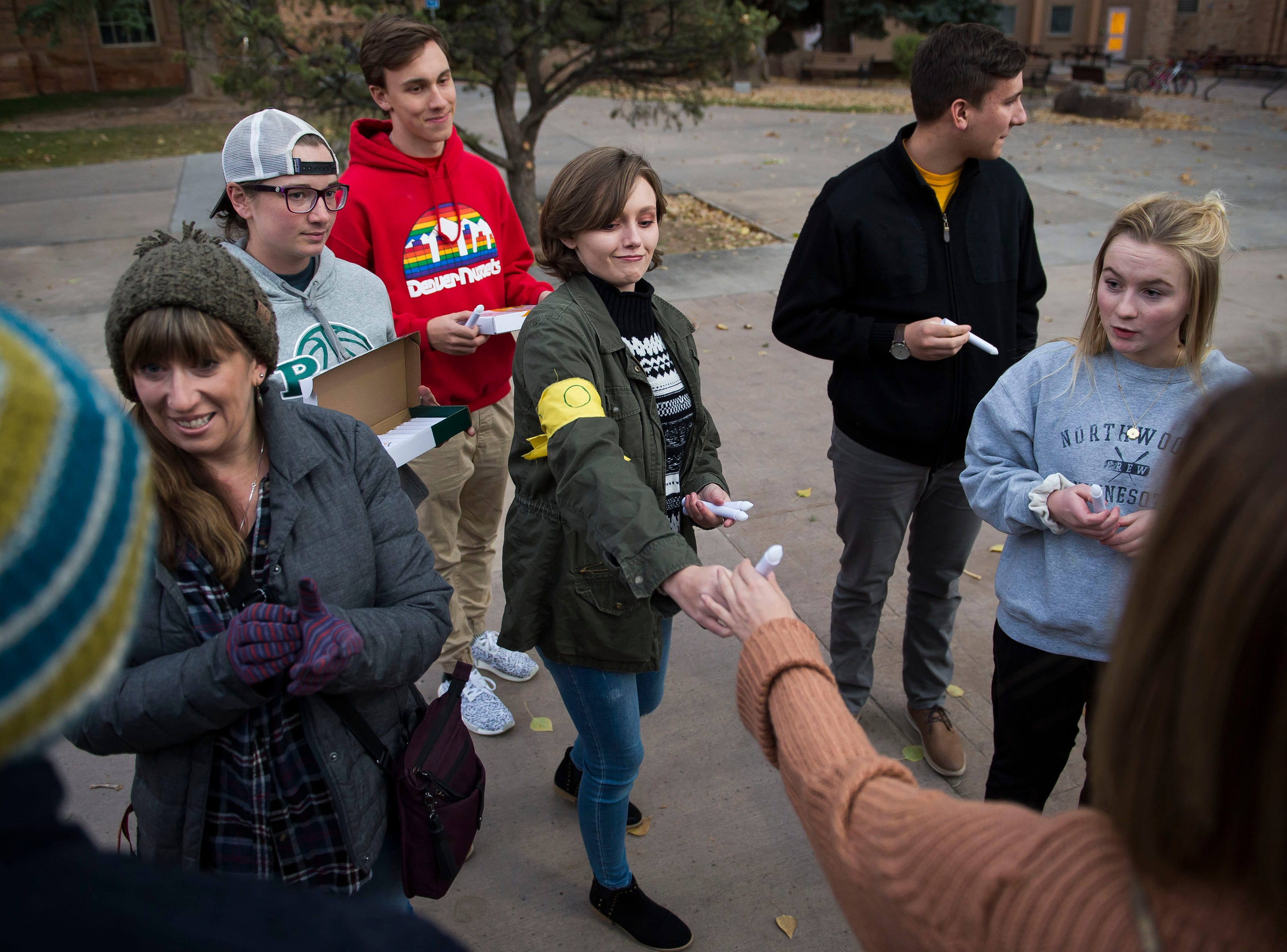 University of Wyoming religious studies junior Danielle DiJohn hands a flameless candle to Laramie resident Aimee Van Cleave before a candlelight vigil on the 20th anniversary of Matthew Shepard's death on Friday, Oct. 12, 2018, at Prexy's Pasture on the University of Wyoming campus in Laramie, Wyo.