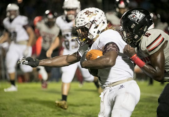 Julian Durham of South Fort Myers grabs Quantavious Brown of Riverdale during the first half on Friday, October 12, 2018, at South Fort Myers High School.