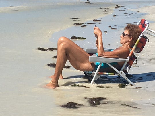With waves gently touching her toes, Fort Myers' Fran Verwilt read on her tablet while relaxing on Fort Myers Beach.