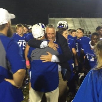Woodmont athletic director Chris Carter (facing) embraces Wildcats coach Jet Turner after Woodmont's 31-28 victory over Westside Friday night.