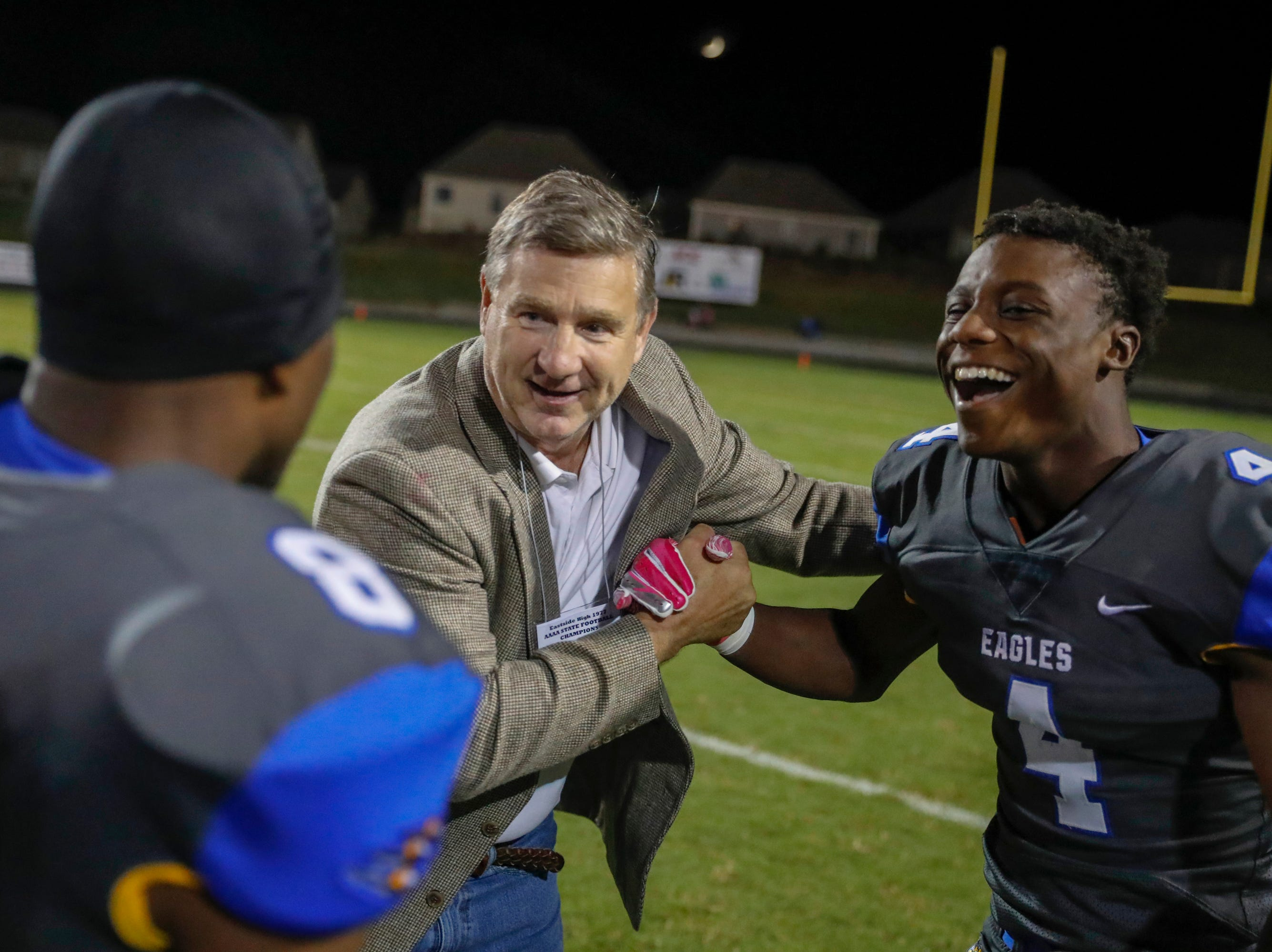 Eastside's Brad Baker of the 77 state championship team is congratulated by Eastside's Payton Mangrum (4) and Eastside's Randy Veal( 8) Friday, October 12, 2018, at Eastside's Carlisle Stadium.
