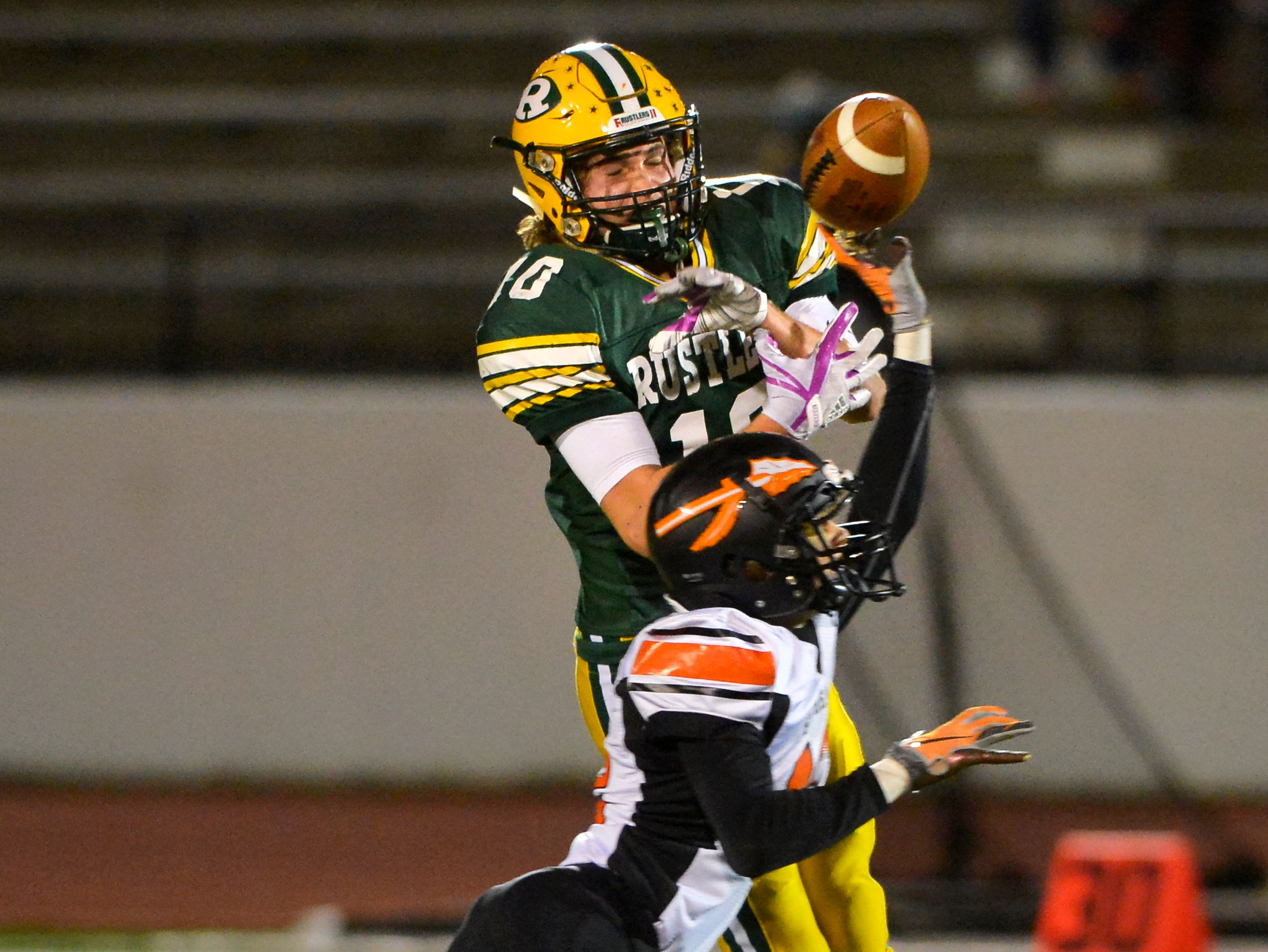 Flathead's Brian Wells breaks up a pass intended for CMR's Tucker Greenwell during Friday night's football game at Memorial Stadium.