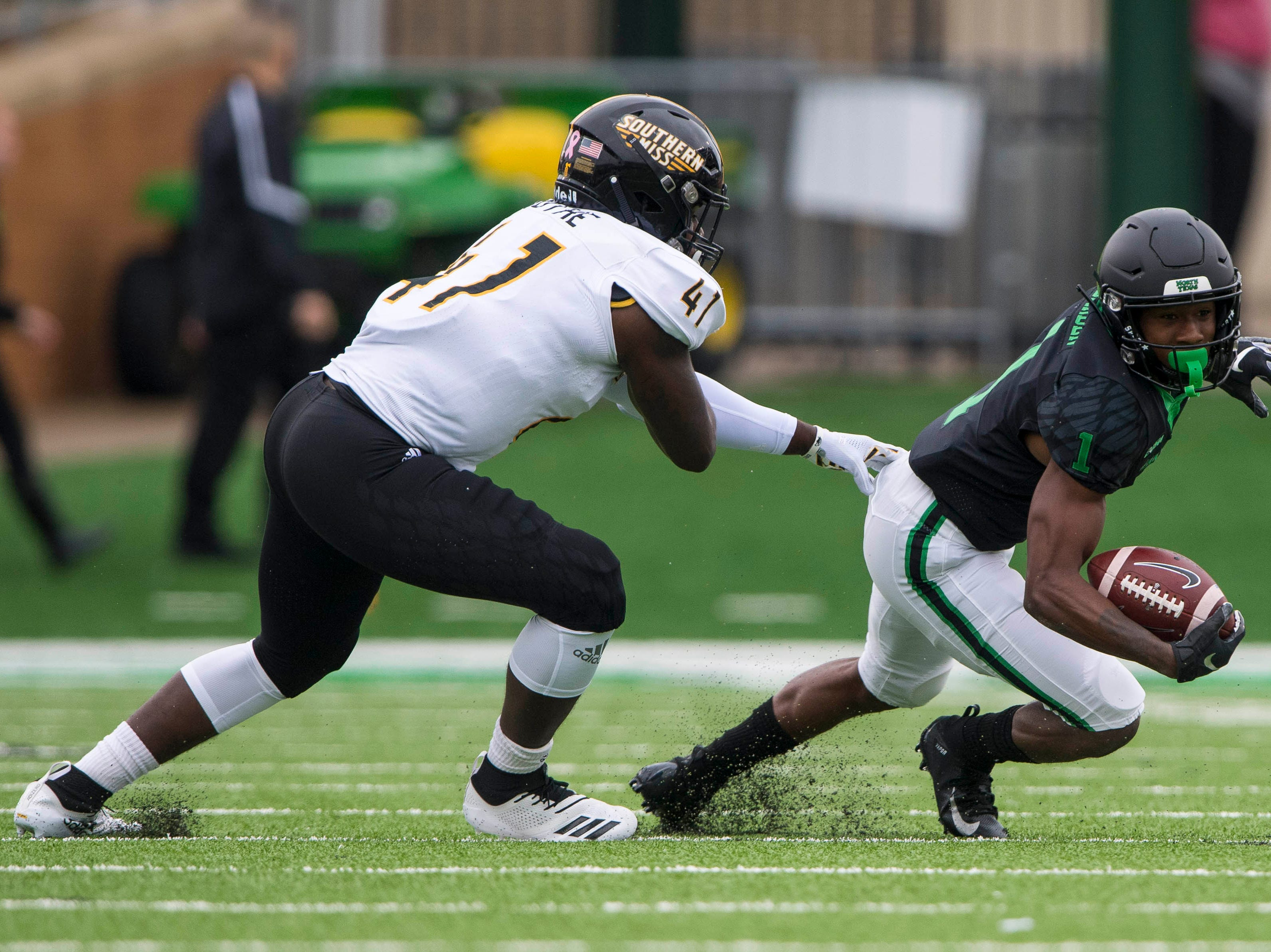 Oct 13, 2018; Denton, TX, USA; North Texas Mean Green wide receiver Jaelon Darden (1) tries to elude Southern Miss Golden Eagles linebacker Racheem Boothe (41) during the first half at Apogee Stadium.