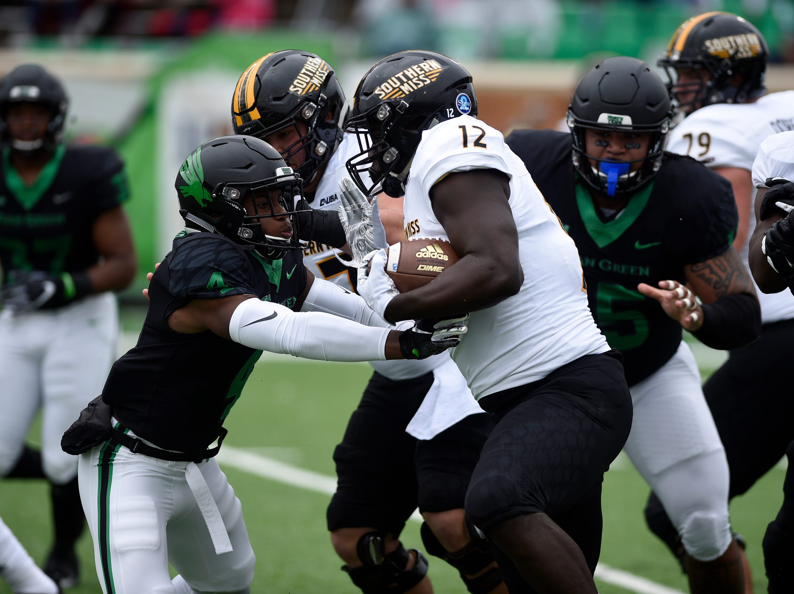 North Texas Mean Green safety Khairi Muhammad (4) charges at Souther Miss running back Steven Anderson (12) during an NCAA college football game at Apogee Stadium in Denton, Texas on Saturday, Oct. 13, 2018.