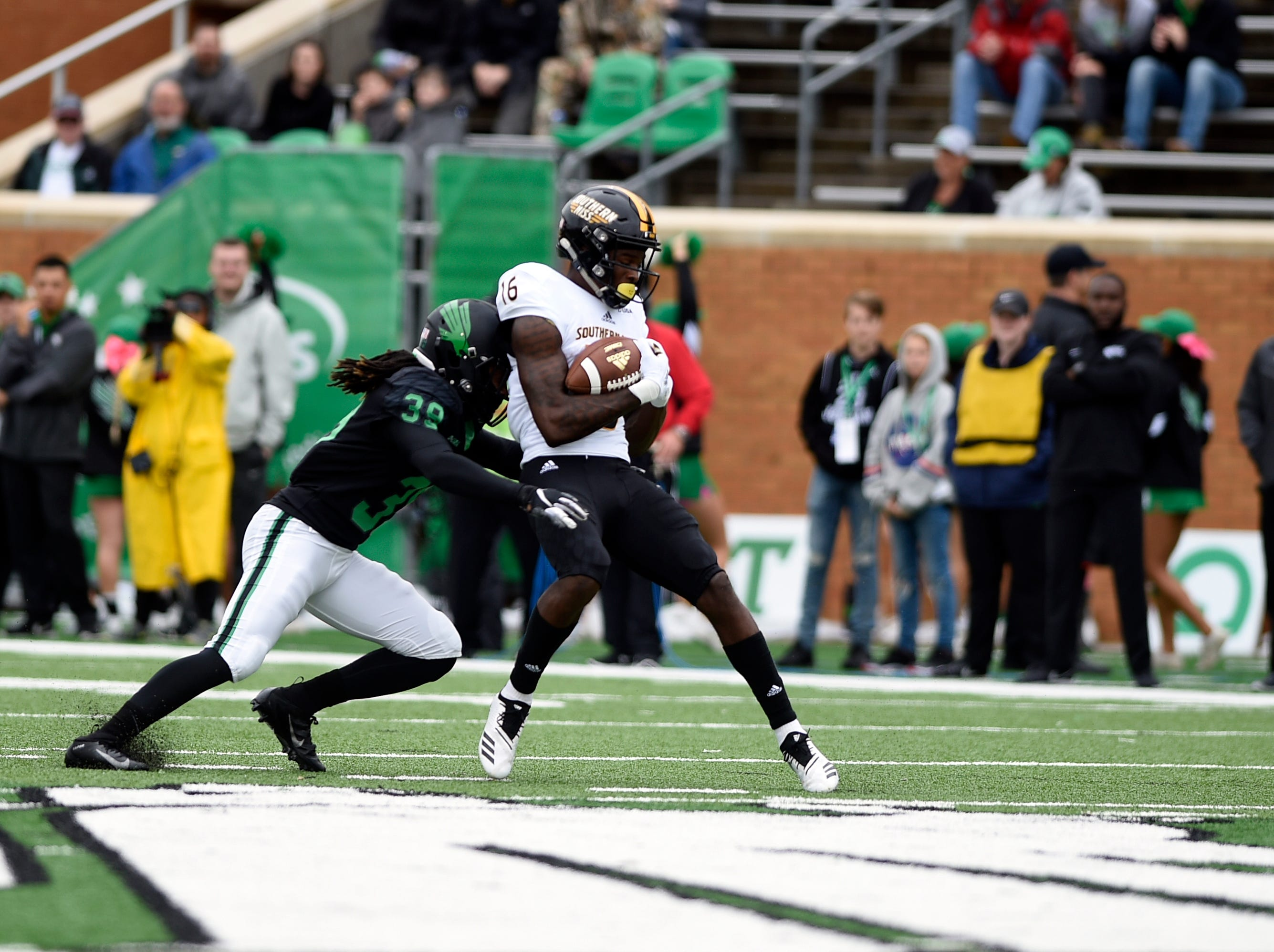North Texas defensive back Jameel Moore (39) tackles Southern Miss wide receiver Quez Watkins (16) during an NCAA college football game at Apogee Stadium in Denton, Texas on Saturday, Oct. 13, 2018.