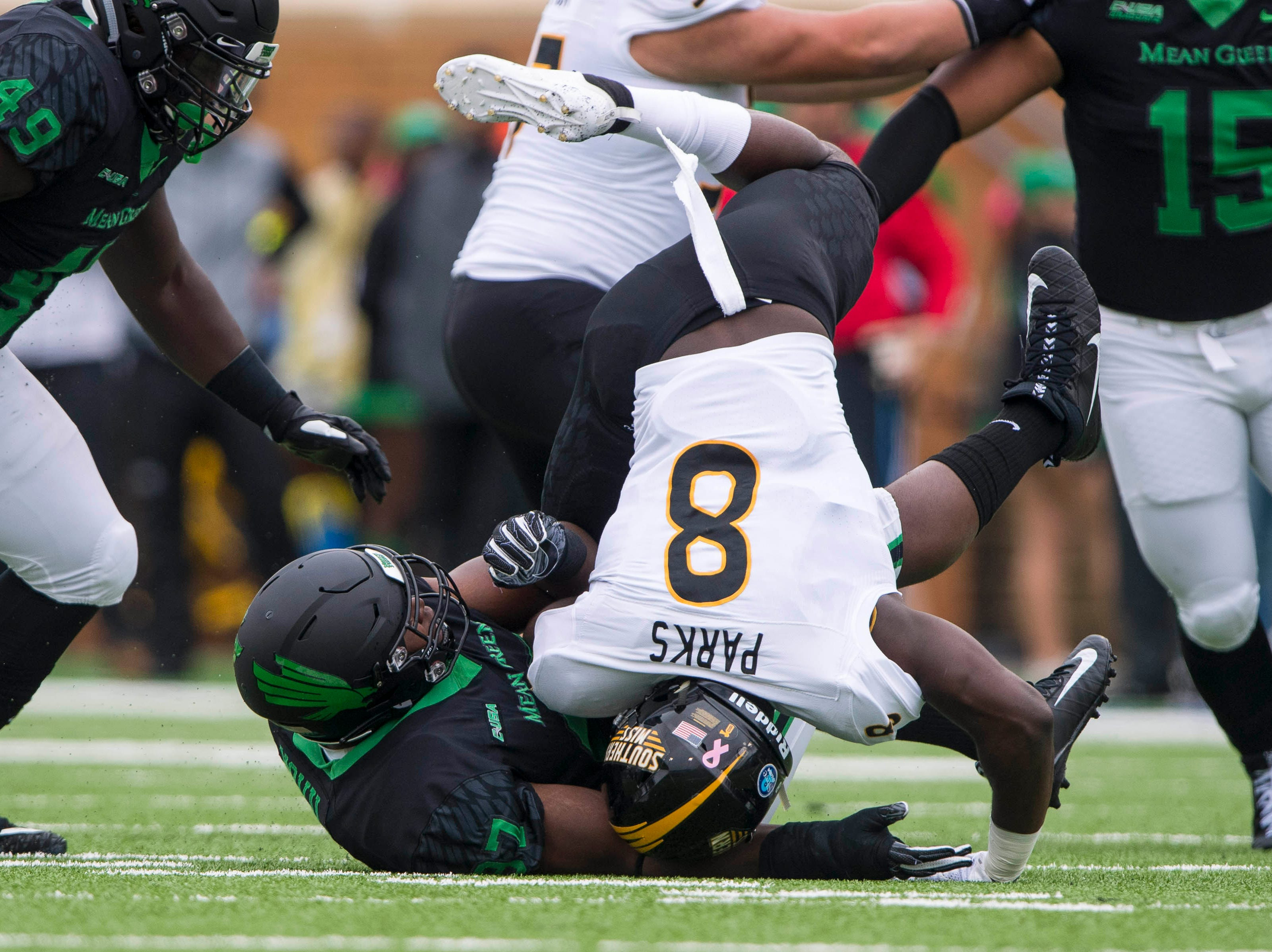 Oct 13, 2018; Denton, TX, USA; North Texas Mean Green defensive lineman Dion Novil (97) tackles Southern Miss Golden Eagles running back Tez Parks (8) during the first half at Apogee Stadium.