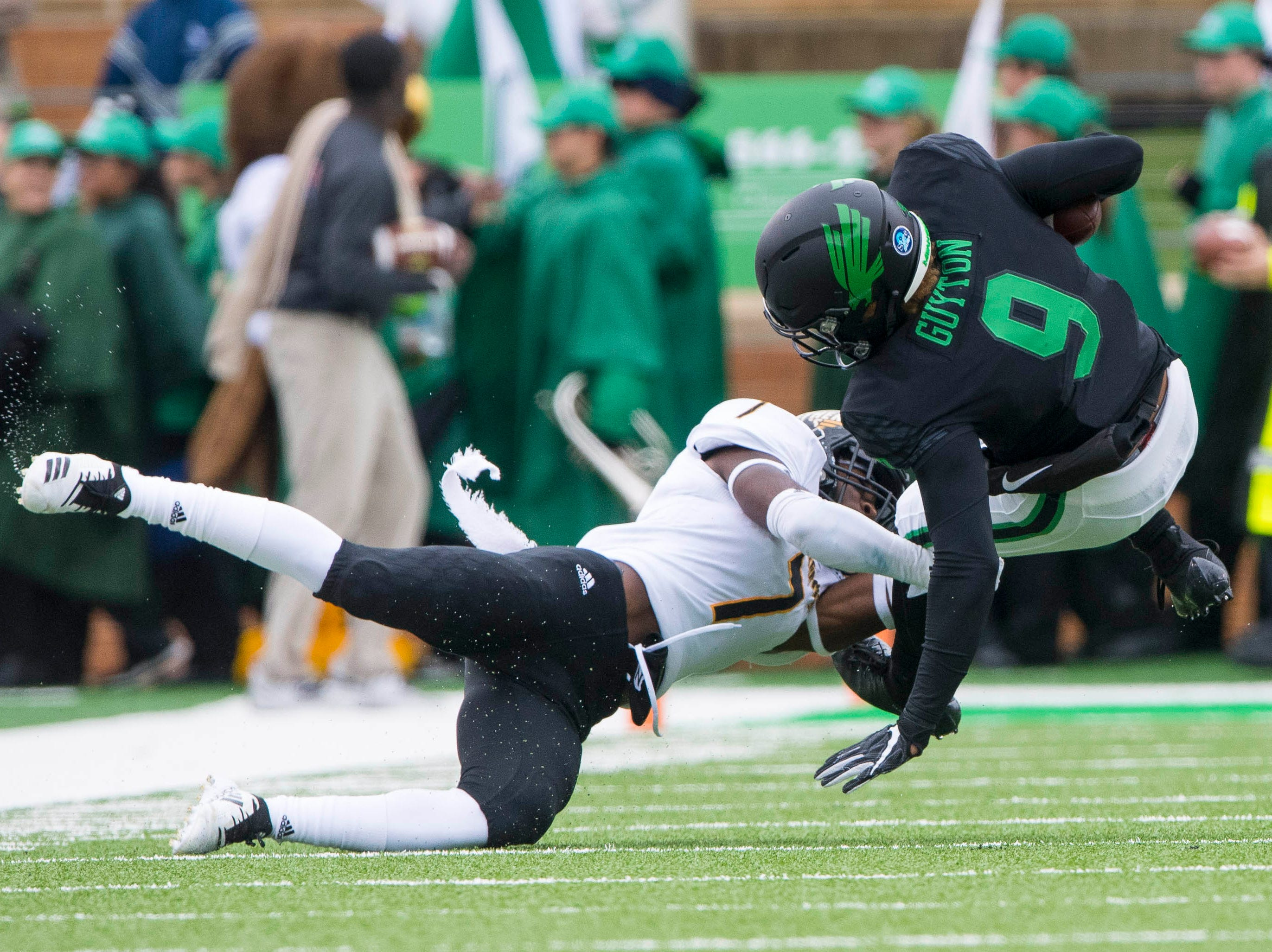 Oct 13, 2018; Denton, TX, USA; North Texas Mean Green wide receiver Jalen Guyton (9) tries to elude Southern Miss Golden Eagles defensive back Ty Williams (7) during the first half at Apogee Stadium.
