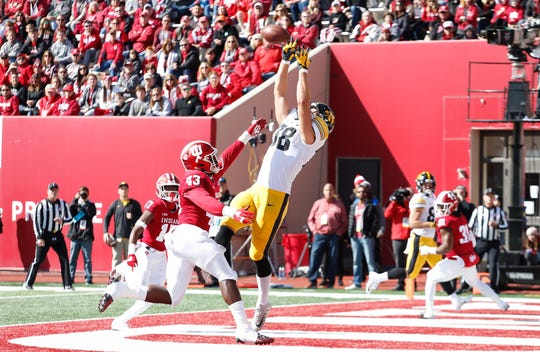 Iowa Hawkeyes tight end T.J. Hockenson (38) catches a pass in the end zone for a touchdown against Indiana Hoosiers linebacker Dameon Willis Jr. (43) during the first quarter at Memorial Stadium.