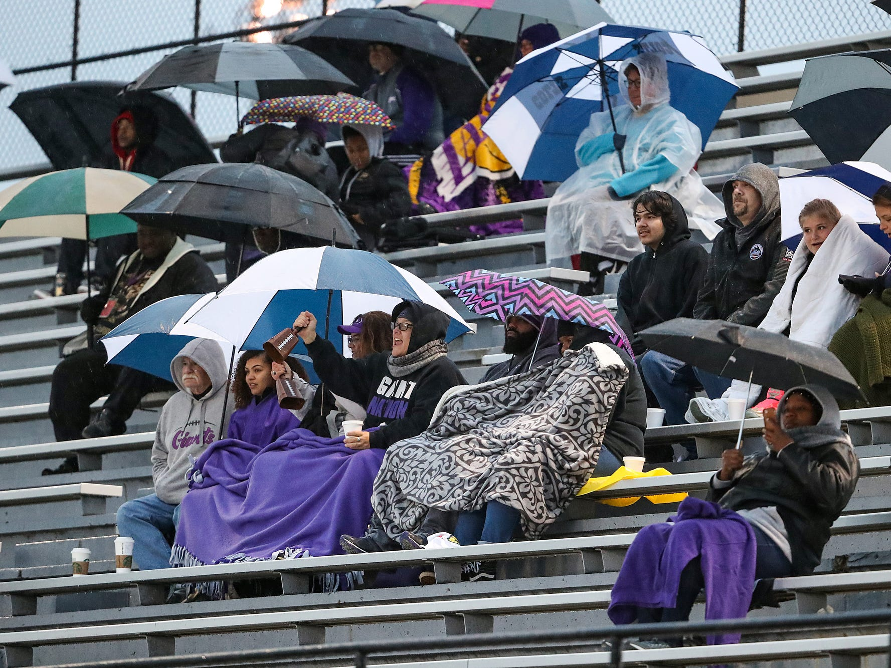 Fans take shelters from the rain and cold in the first half of the game at North Central High School in Indianapolis, Oct. 12, 2018.