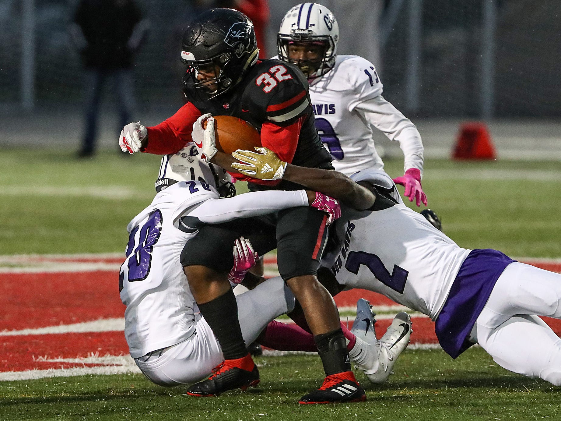 Ben Davis Giants Chris Peters (28) and Michael Adams (2) tackle North Central Panthers running back Alexander Tarver (32) in the first half of the game at North Central High School in Indianapolis, Oct. 12, 2018.