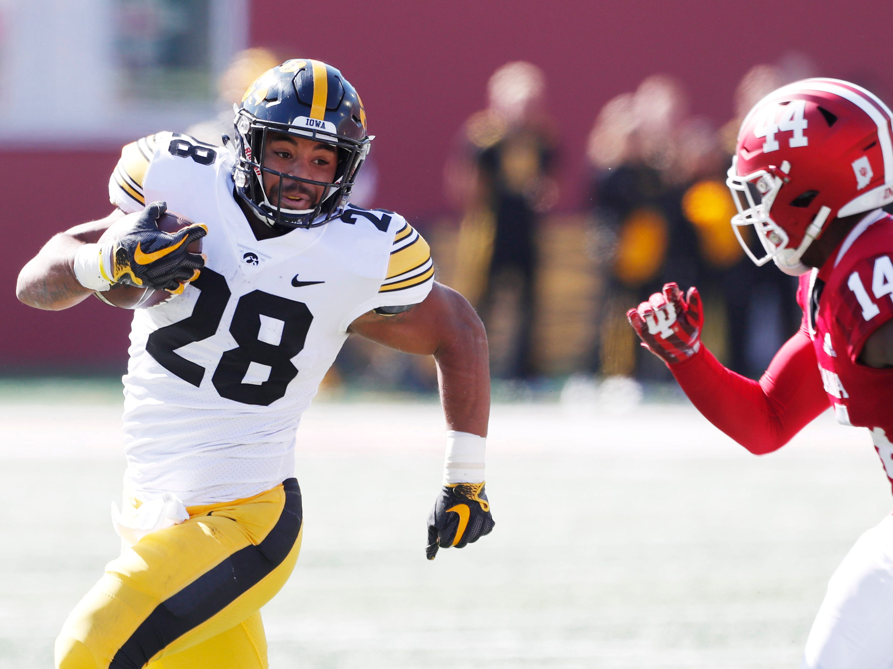 Iowa Hawkeyes running back Toren Young (28) runs with the ball against Indiana Hoosiers defensive back Andre Brown Jr. (14) during the first quarter at Memorial Stadium .