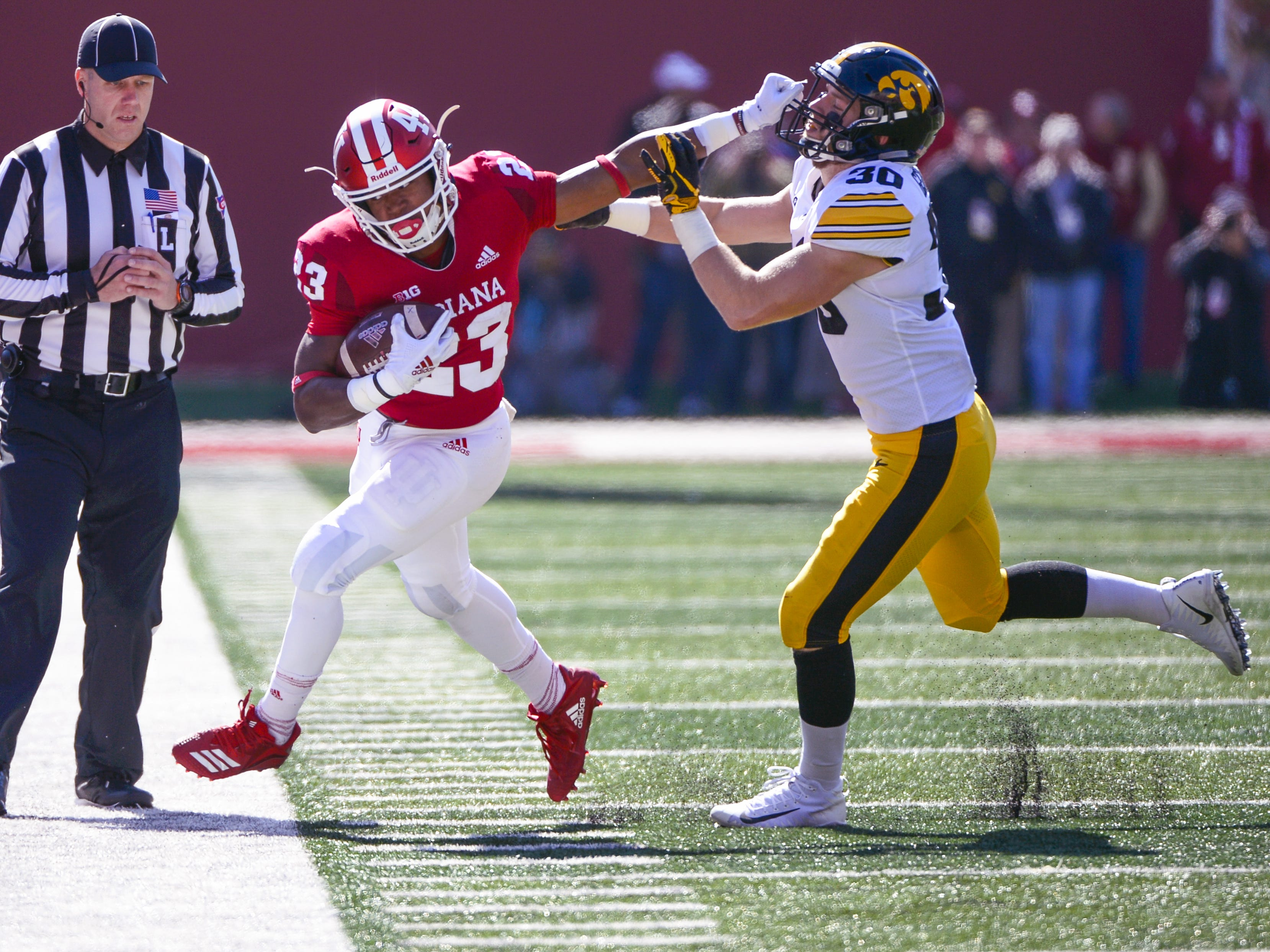 Indiana Hoosiers running back Ronnie Walker Jr. (23) stiff arms a defender during the game against Iowa at Memorial Stadium in Bloomington, Ind., on Saturday, Oct. 13, 2018.