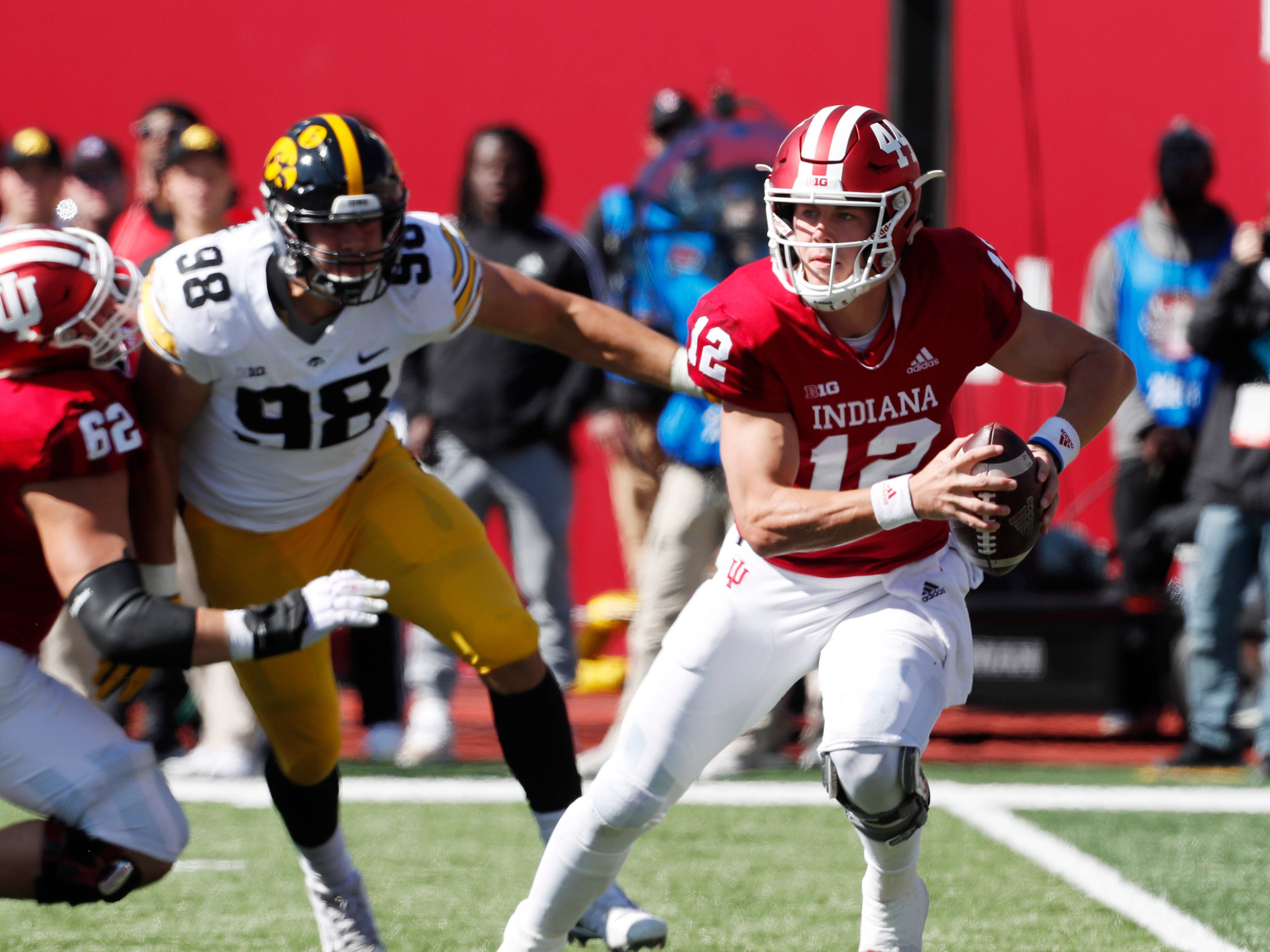 Indiana Hoosiers quarterback Peyton Ramsey (12) rolls out to throw a pass against the Iowa Hawkeyes during the first quarter at Memorial Stadium .