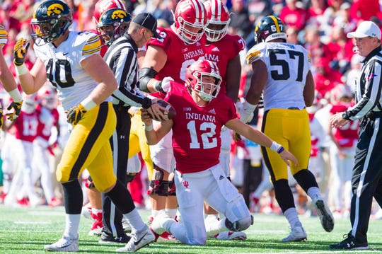 Indiana quarterback Peyton Ramsey (12) is helped to his feet by his teammates after being sacked by the Iowa defense during the first half of an NCAA college football game Saturday, Oct. 13, 2018, in Bloomington, Ind.
