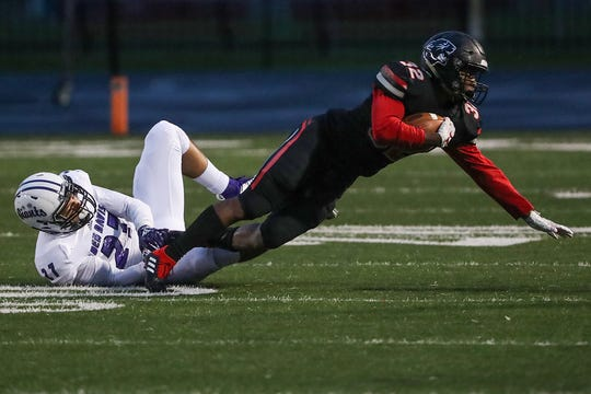 Ben Davis Giants middle linebacker Kameron Kelly (27) pulls down North Central Panthers running back Alexander Tarver (32) in the first half of the game at North Central High School in Indianapolis, Oct. 12, 2018.