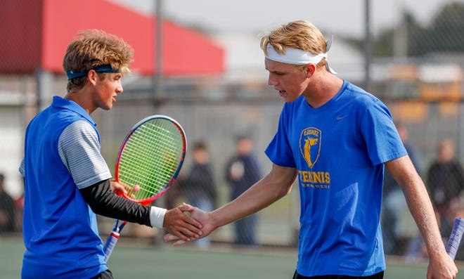 Carmel High School's Timmy Dixon, left, low fives doubles partner Garrett Lloyd, right, in a match against Nathan Branaman and Brian McAuley during the 52nd Annual IHSAA Boys Team Tennis State Finals, held at North Central High School in Indianapolis on Saturday, October 13, 2018.