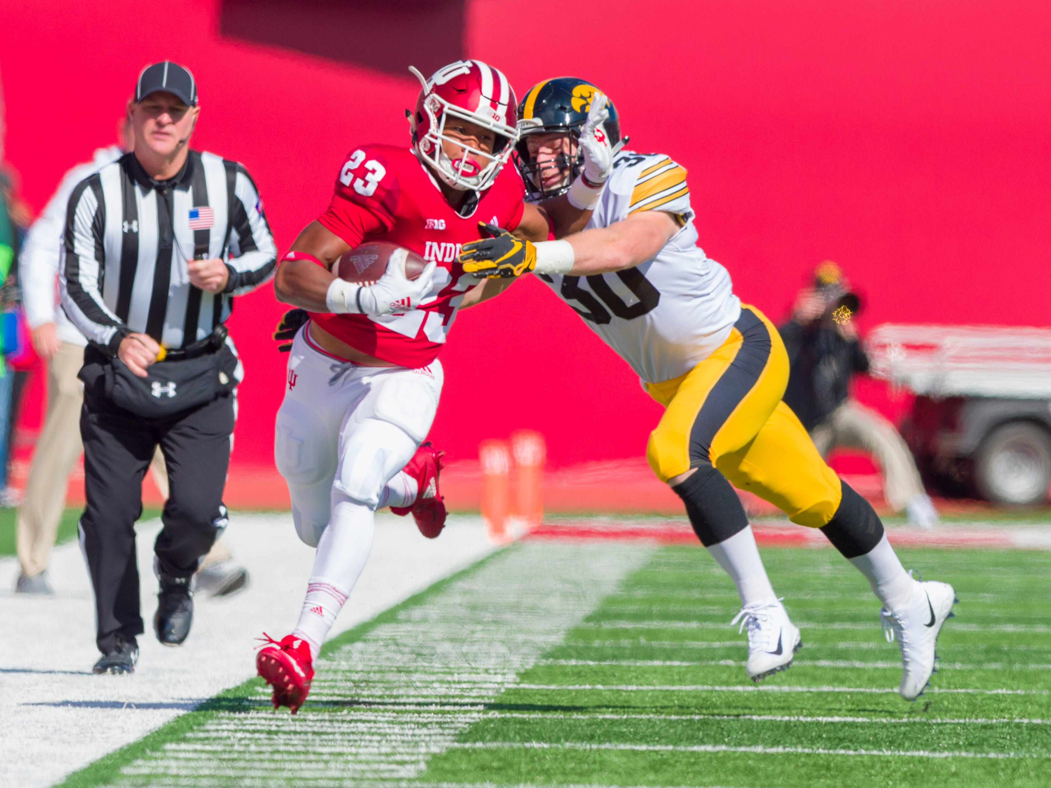 Indiana running back Ronnie Walker Jr. (23) runs the ball up the sideline as he's grabbed by Iowa defensive back Jake Gervase (30) during the first half of an NCAA college football game Saturday, Oct. 13, 2018, in Bloomington, Ind. (AP Photo/Doug McSchooler)