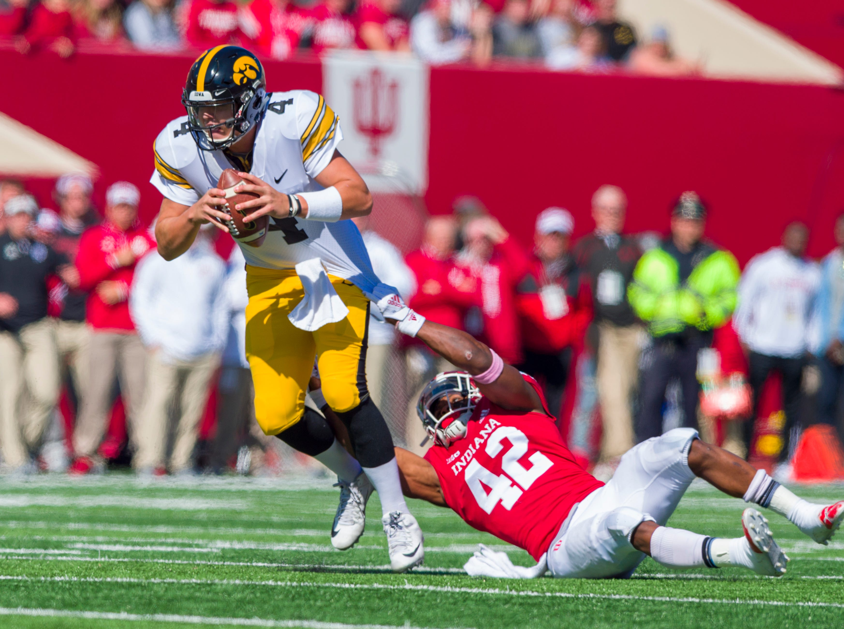 Indiana defensive back Marcelino Ball (42) tries to sack Iowa quarterback Nate Stanley (4) during the first half of an NCAA college football game Saturday, Oct. 13, 2018, in Bloomington, Ind. (AP Photo/Doug McSchooler)
