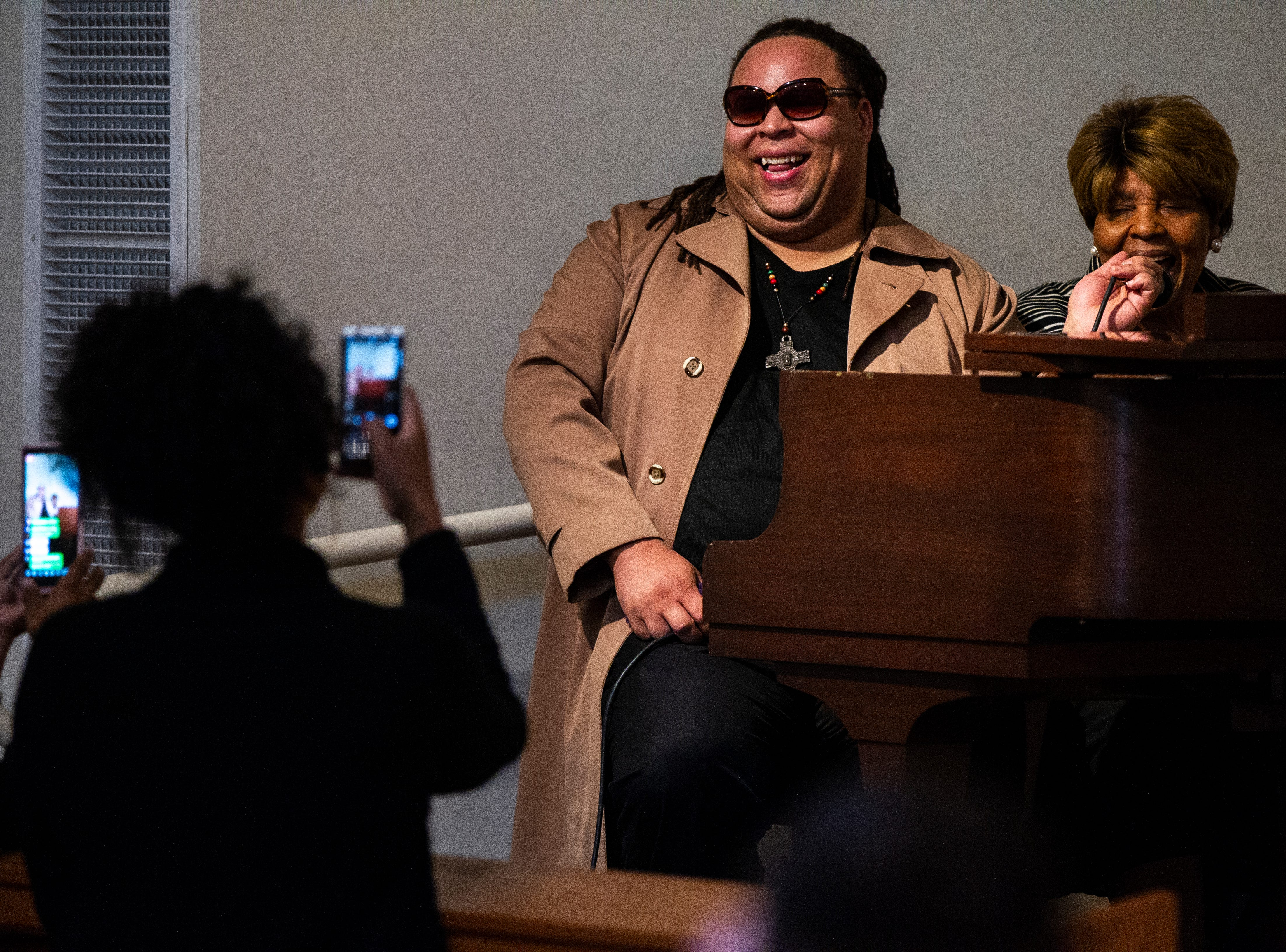 James Teague holds a microphone for his mother Mary Teague as she performs a song during a swearing in ceremony for Iowa City councilor Bruce Teague on Saturday, Oct. 13, 2018, at the Church of Nazarene on Wade Street in Iowa City.