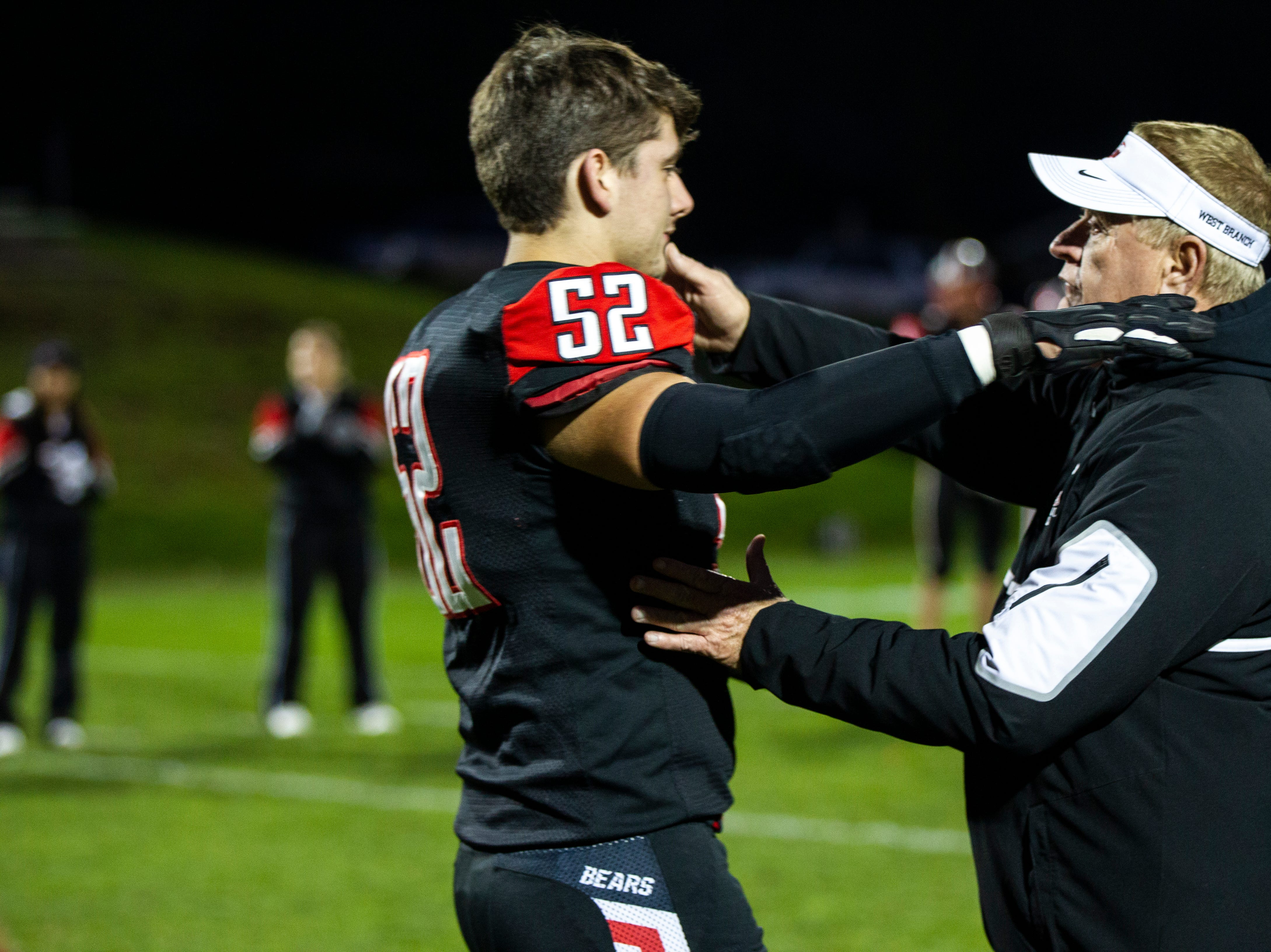 West Branch football head coach Butch Pedersen embraces senior lineman Jaden Hierseman (52) before a Class A varsity football game on Friday, Oct. 12, 2018, at the Little Rose Bowl in West Branch, Iowa.