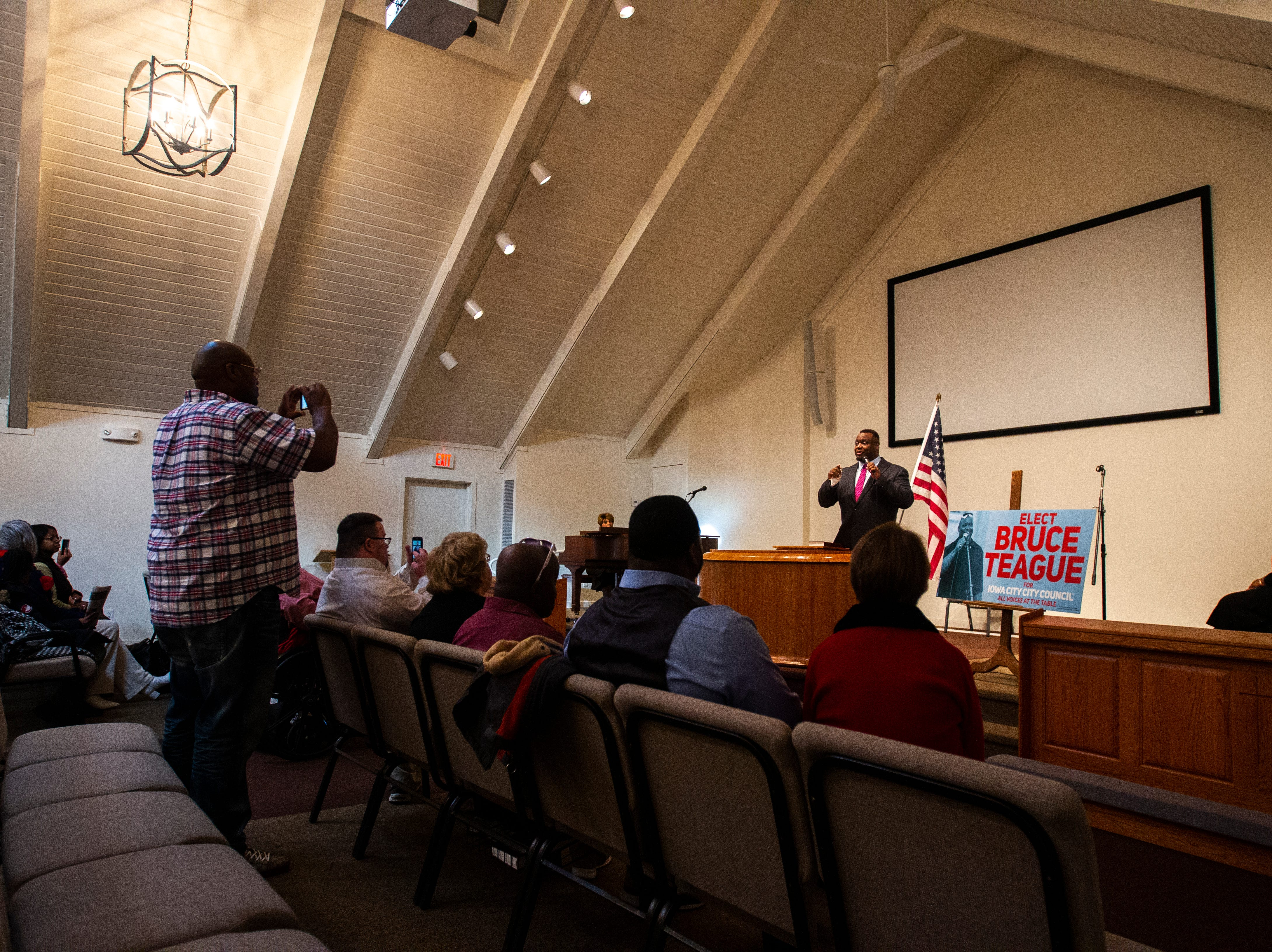 Iowa City councilor Bruce Teague thanks supporters while his cousin, Pastor Harrold Washington, takes a photo after a swearing in ceremony on Saturday, Oct. 13, 2018, at the Church of Nazarene on Wade Street in Iowa City.