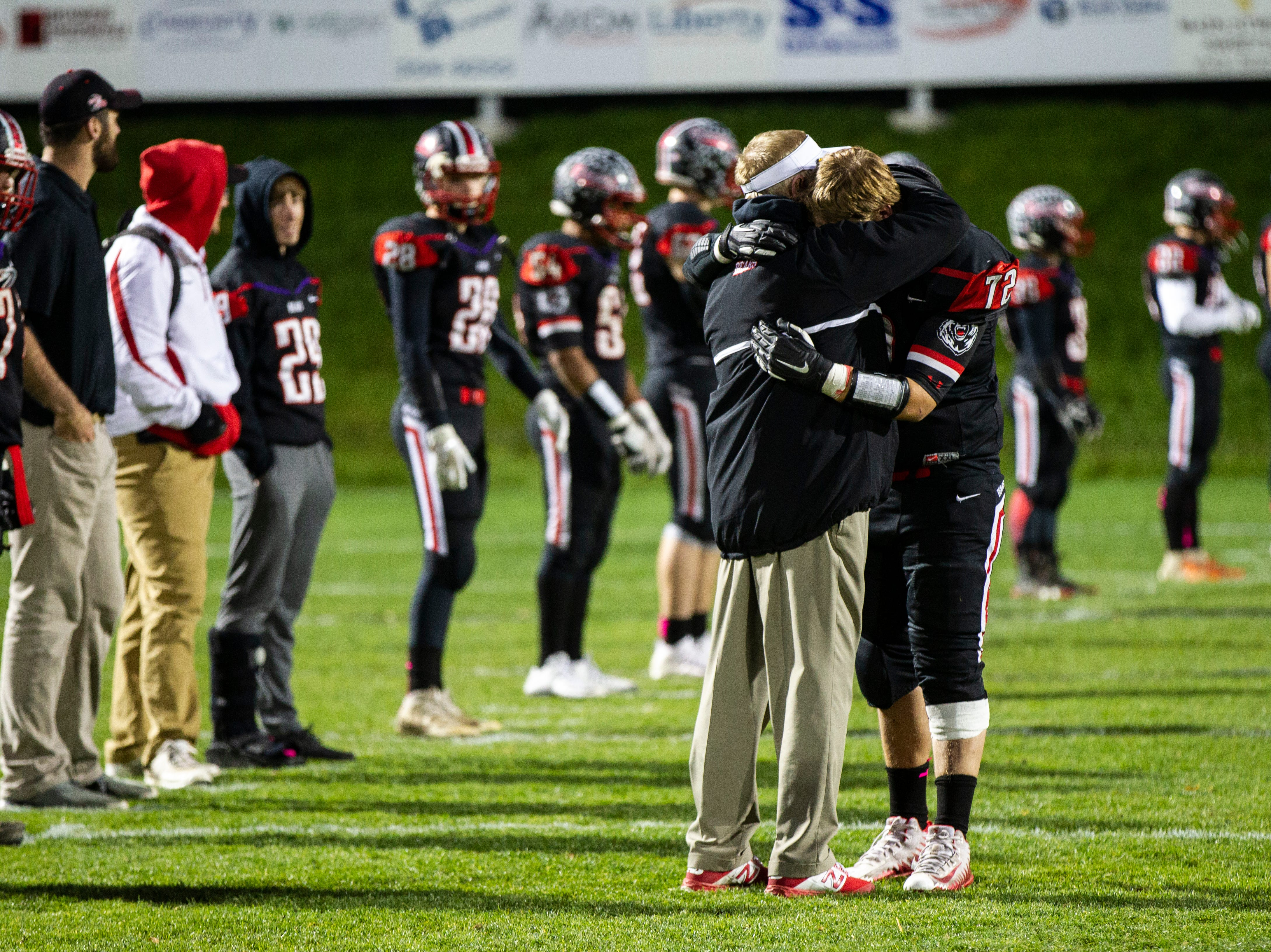 West Branch football head coach Butch Pedersen embraces senior lineman Drake Bloem (72) before a Class A varsity football game on Friday, Oct. 12, 2018, at the Little Rose Bowl in West Branch, Iowa.
