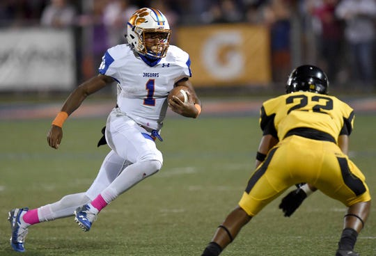 Madison Central quarterback Jimmy Holiday (1) looks to get by Starkville's Justice Robinson (22) on Friday, October 12, 2018, at Madison Central High School in Madison, Miss.