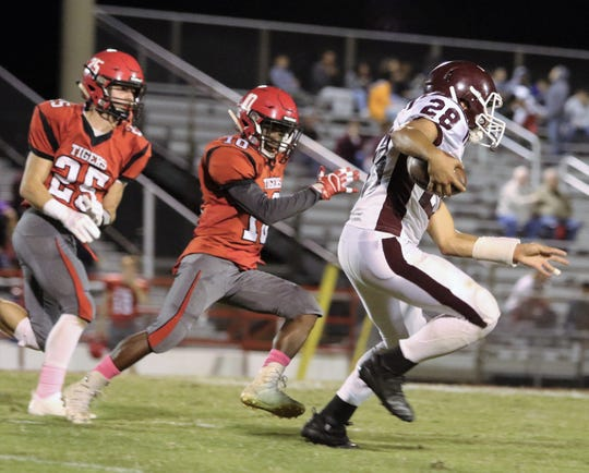 Hardin County's John Whitley (28) runs away from Lexington defenders on Oct. 12, 2018.