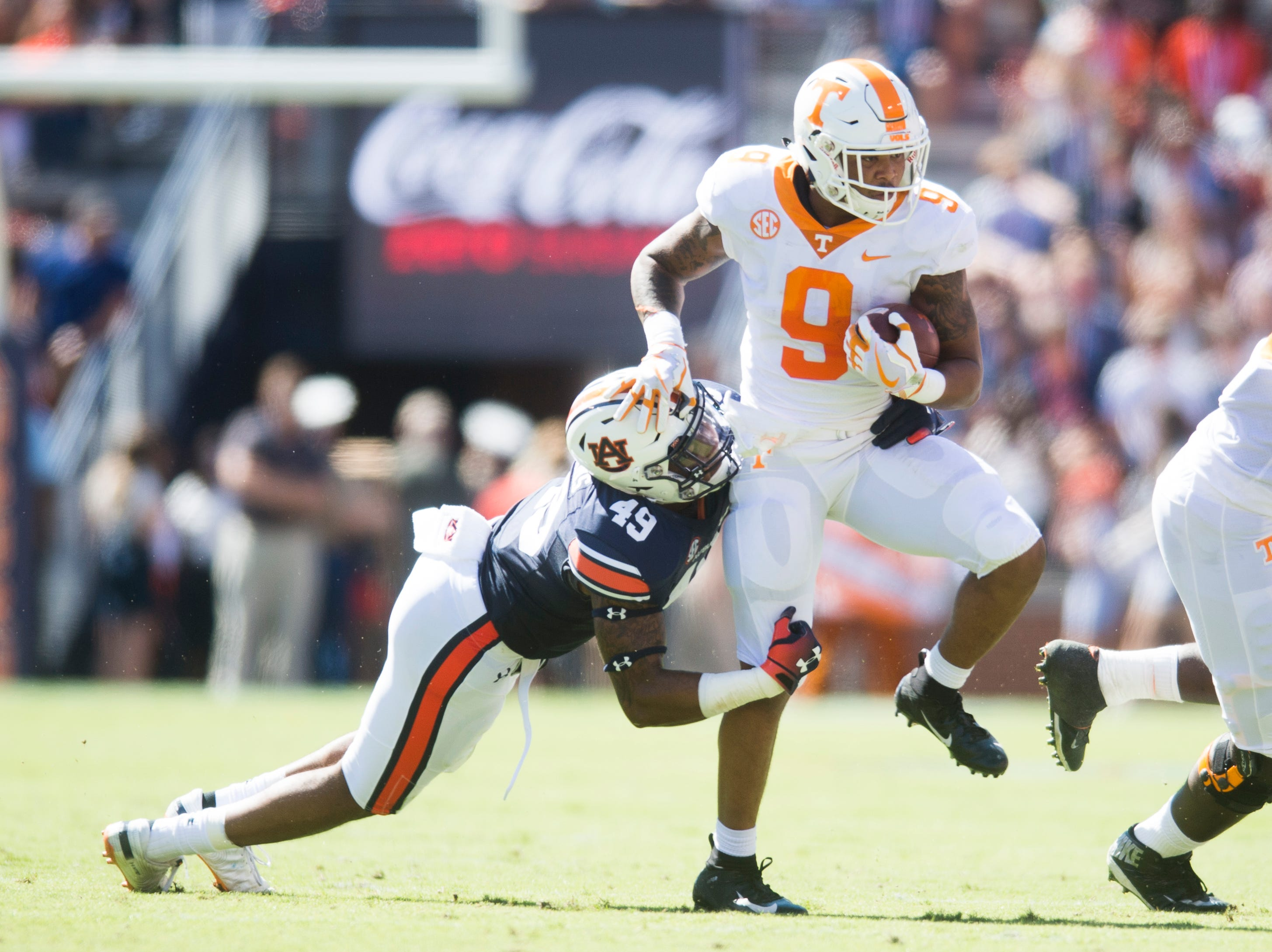 Tennessee running back Tim Jordan (9) runs with the ball as Auburn linebacker Darrell Williams (49) tries to stop him during a game between Tennessee and Auburn at Jordan-Hare Stadium in Auburn, Alabama on Saturday, October 13, 2018.