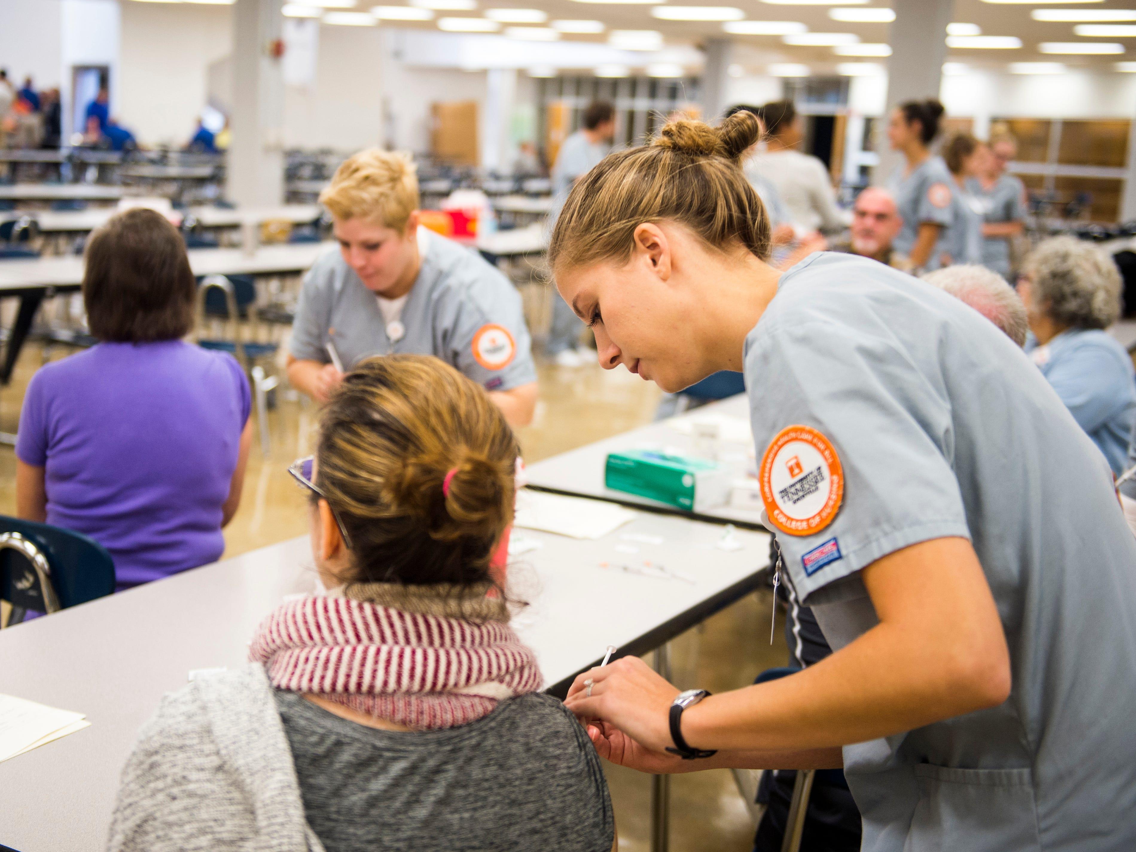 UT nursing student Emily Easterly administers a flu shot at Farragut High School during Free Flu Shot Saturday on Saturday, October 12, 2018.