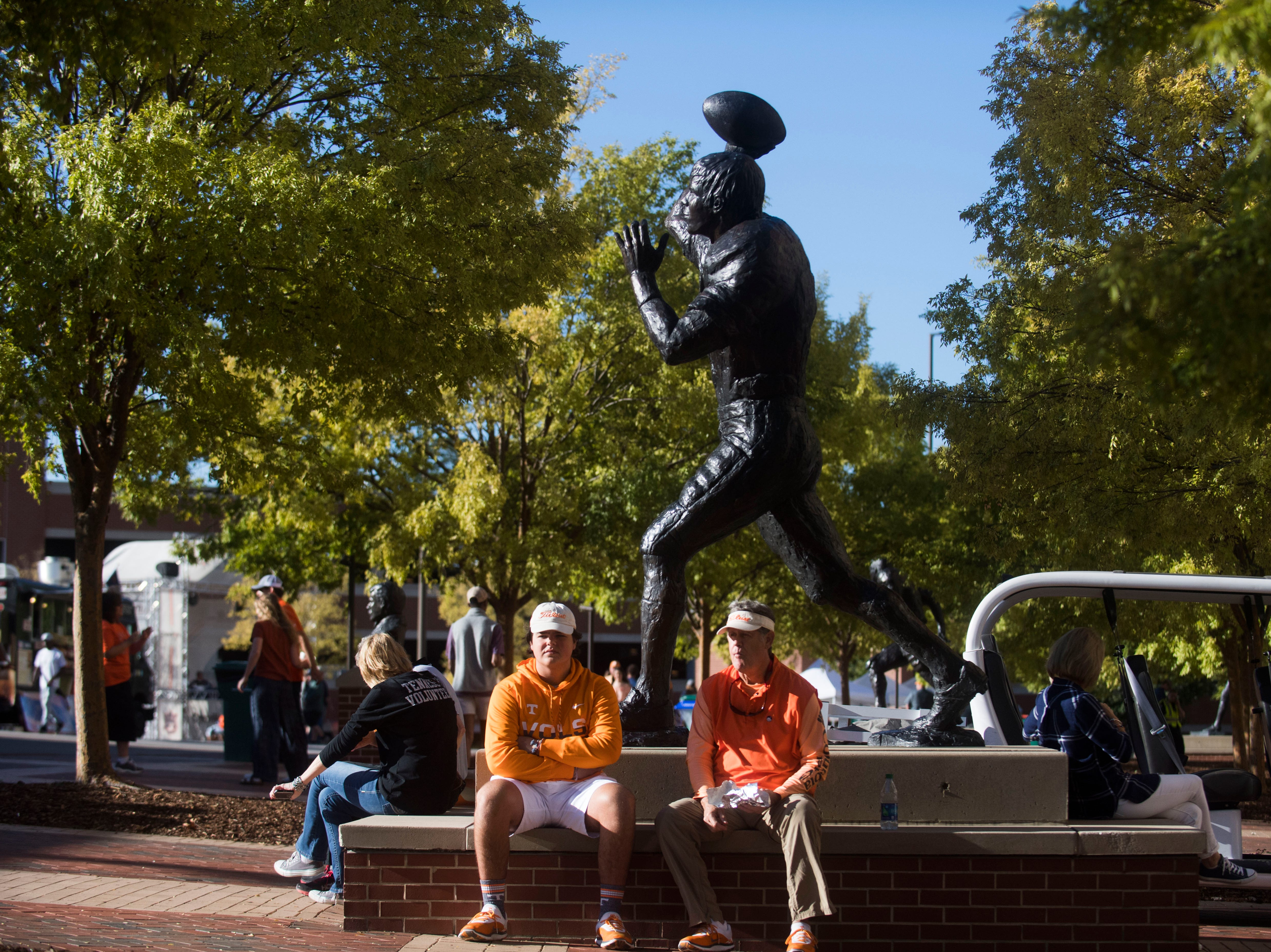 Vols fans sit next to a statue before a game between Tennessee and Auburn at Jordan-Hare Stadium in Auburn, Ala. Saturday, Oct. 13, 2018.