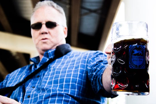 Steve Brewer, with one arm in a sling, holds a beer glass during a steinholding contest at the inaugural Old City Oktoberfest on Saturday. Brewer won the male competition, while his wife, Chris, won the female competition.