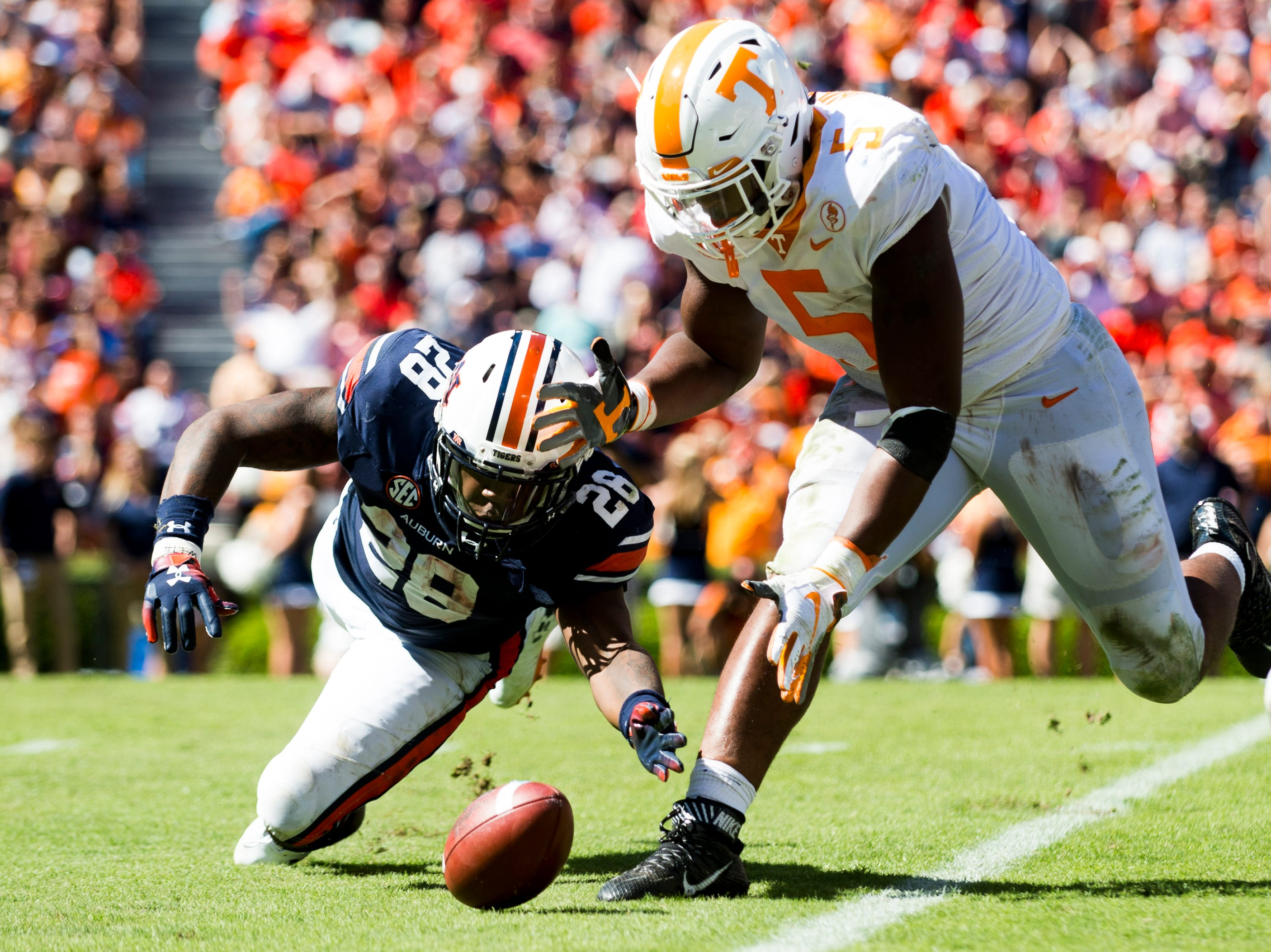 Auburn running back JaTarvious Whitlow (28) and Tennessee defensive lineman Kyle Phillips (5) chase after a fumble during a game between Tennessee and Auburn at Jordan-Hare Stadium in Auburn, Alabama on Saturday, October 13, 2018.