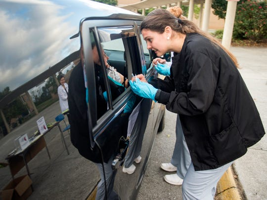 University of Tennessee nursing student Kathryn Rack administer flu shots in a drive thru fashion for people unable to get out of their cars at Farragut High School during Free Flu Shot Saturday on Saturday, October 12, 2018.