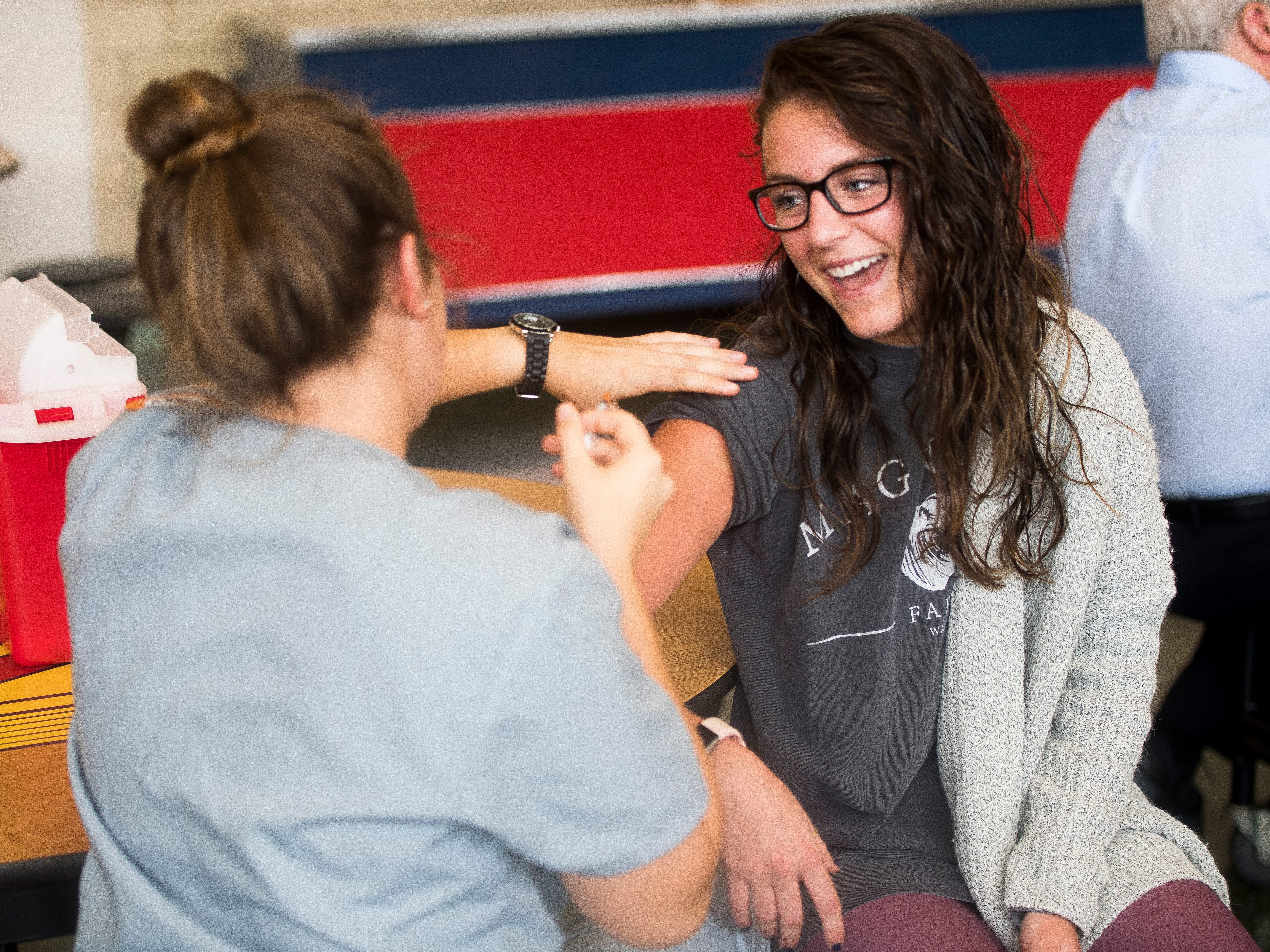 Brittni Woodall, right, laughs as she receives a flu shot from UT nursing student Ashleigh Guidara at West High School during Free Flu Shot Saturday on Saturday, October 12, 2018.
