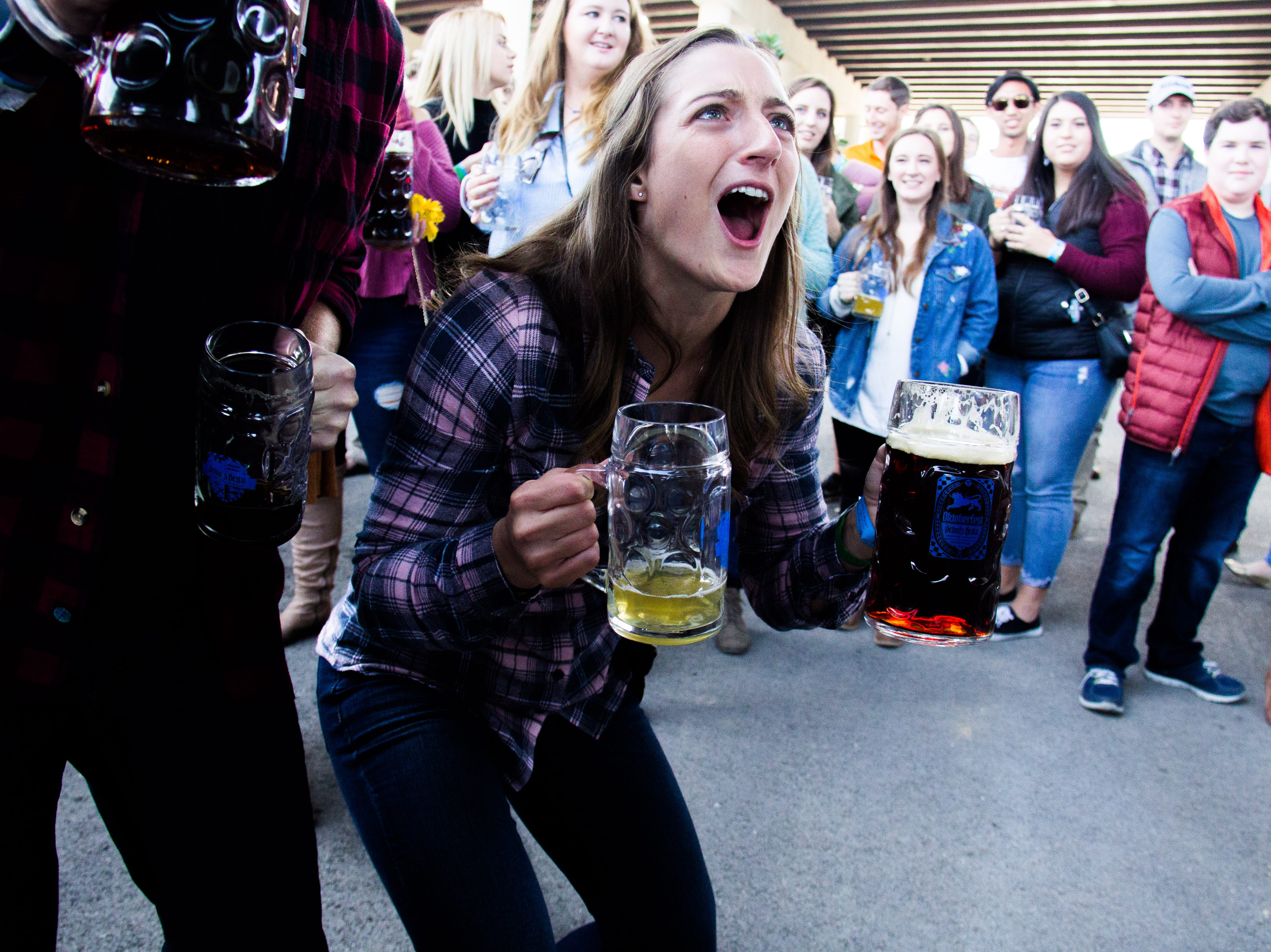 A festival-goer cheers during a steinholding contest at the inaugural Old City Oktoberfest on Oct. 13, 2018.