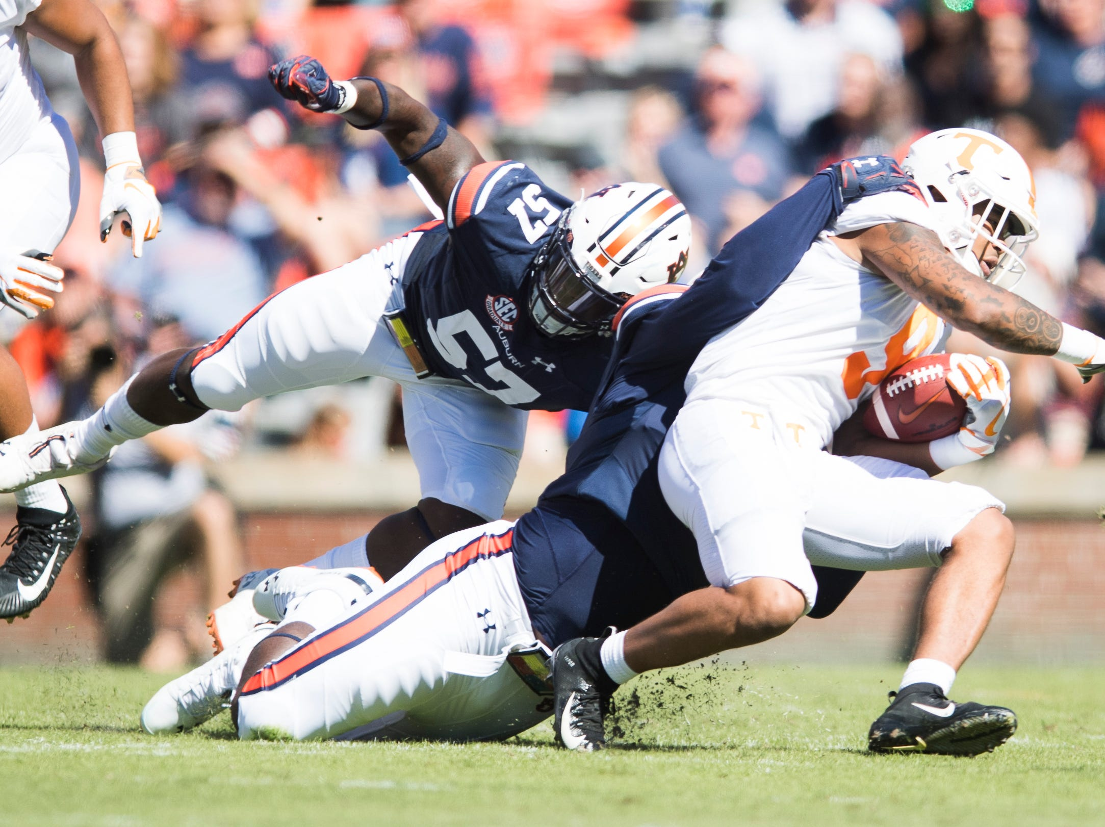 Tennessee running back Tim Jordan (9) is taken down by Auburn defensive lineman Marlon Davidson (3) and Auburn linebacker Deshaun Davis (57) during a game between Tennessee and Auburn at Jordan-Hare Stadium in Auburn, Alabama on Saturday, October 13, 2018.