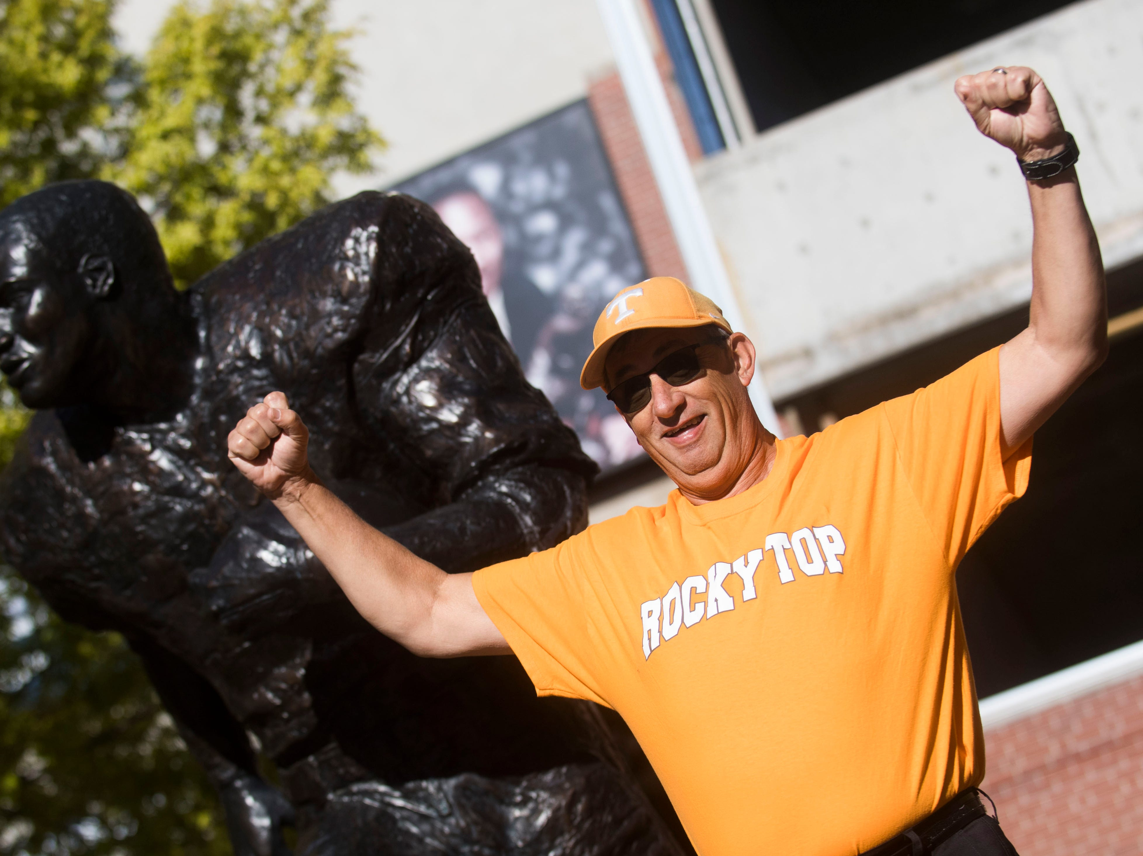 Kevin Moore of Cleveland, Tenn. poses for a photo with a statue before a game between Tennessee and Auburn at Jordan-Hare Stadium in Auburn, Ala. Saturday, Oct. 13, 2018.