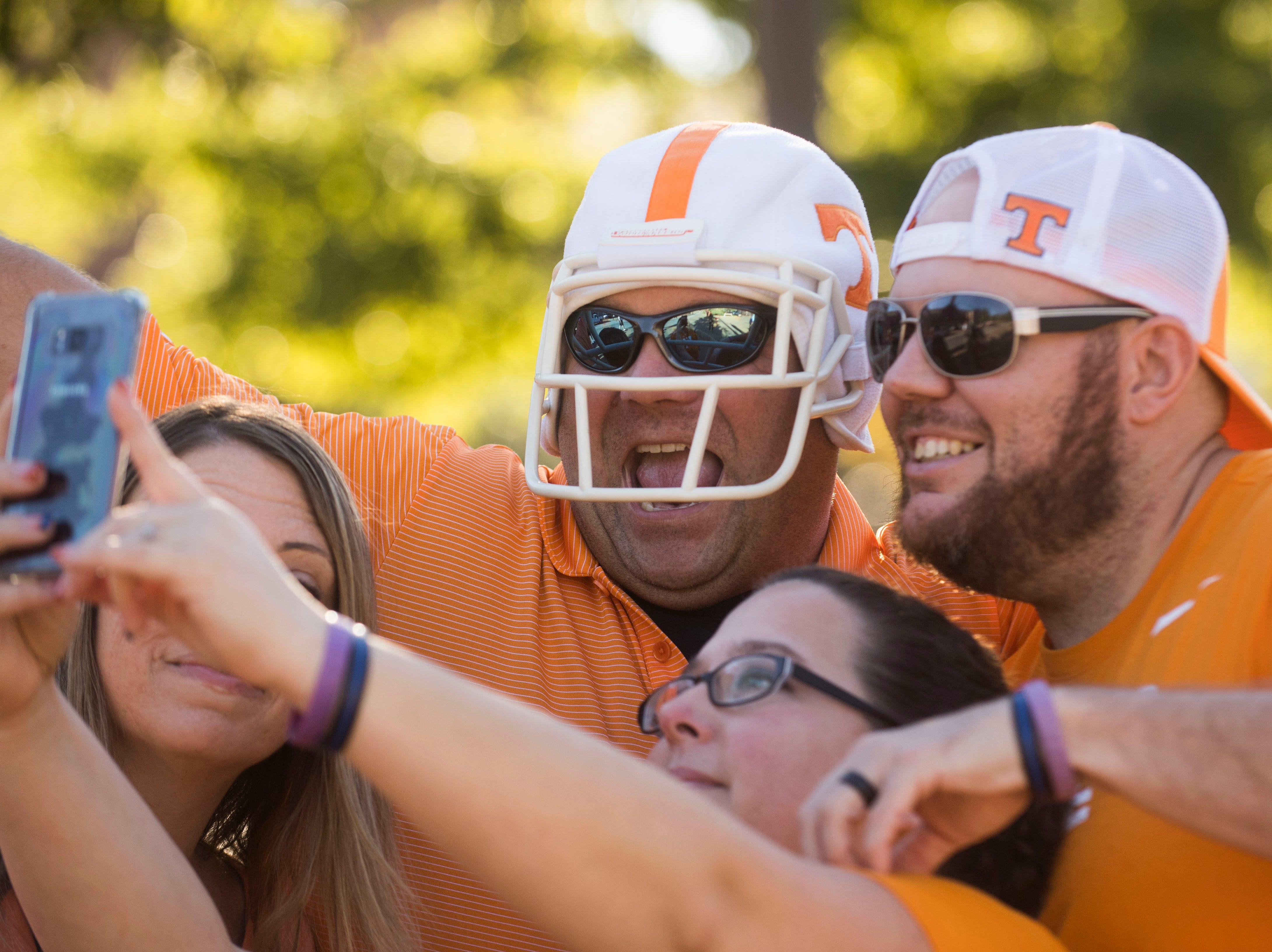 At left Derek Copeland, of Alcoa, Tenn. poses for a photo with friends before a game between Tennessee and Auburn at Jordan-Hare Stadium in Auburn, Ala. Saturday, Oct. 13, 2018.