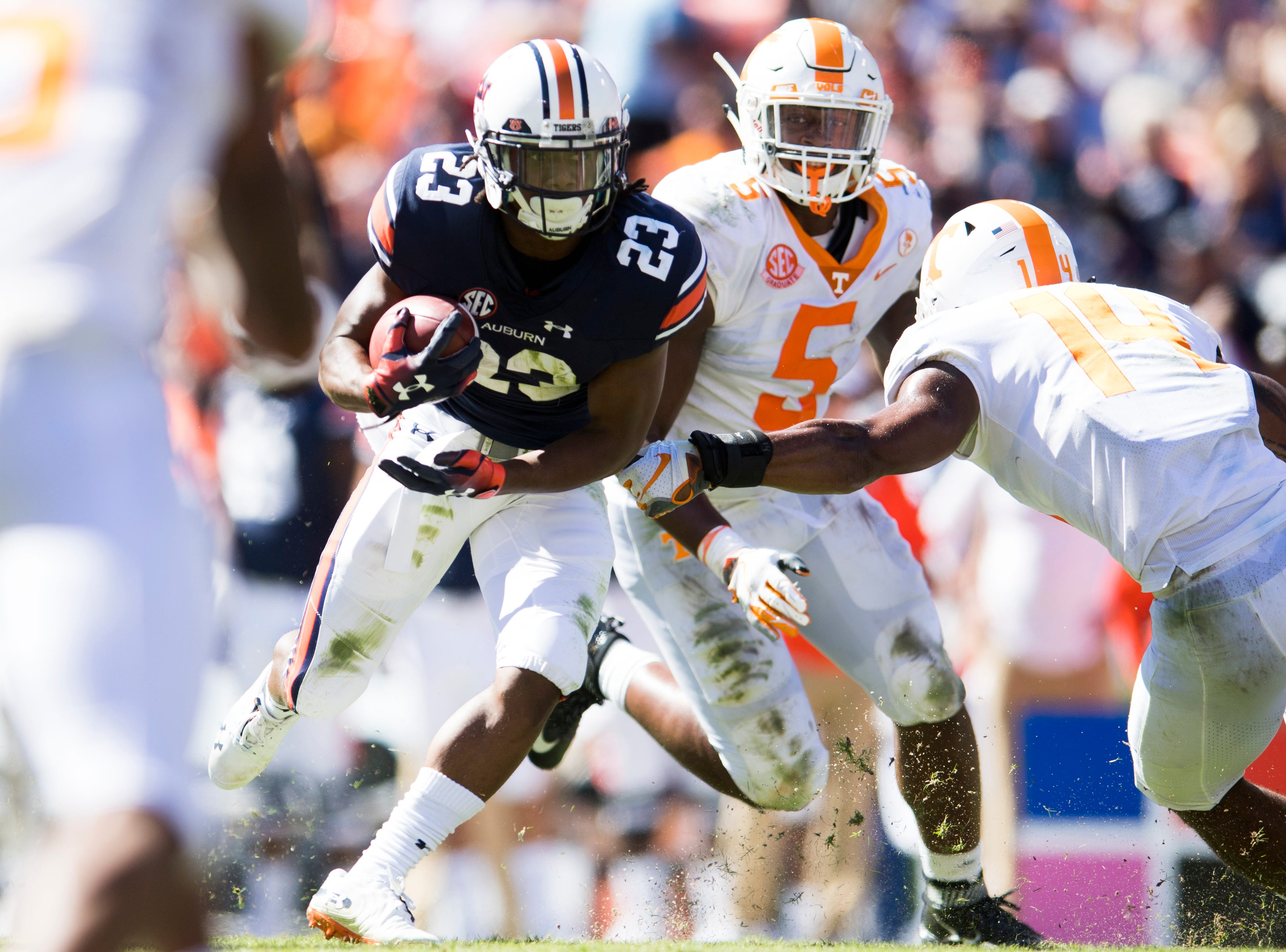 Auburn wide receiver Ryan Davis (23) tries to evade Tennessee linebacker Quart'e Sapp (14) and Tennessee defensive lineman Kyle Phillips (5) during a game between Tennessee and Auburn at Jordan-Hare Stadium in Auburn, Alabama on Saturday, October 13, 2018.