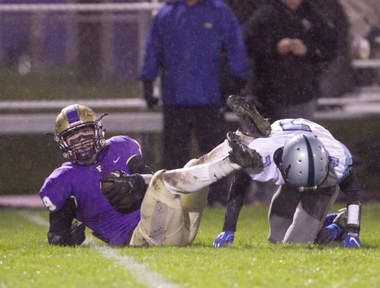 Fowlerville's Andrew McFadden is tackled by Lansing Catholic's Connor Doyle after catching a pass on Friday, Oct. 12, 2018.