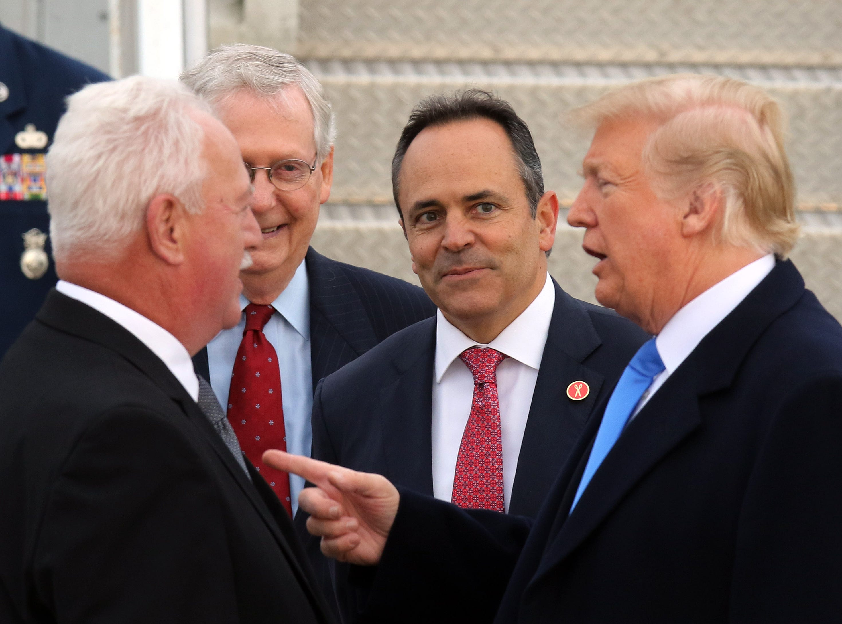 Sen. Mitch McConnell and Gov. Bevin, middle, look on as President Trump, right, greets an individual near Air Force One at Bluegrass Airport in Lexington, Oct. 13, 2018.