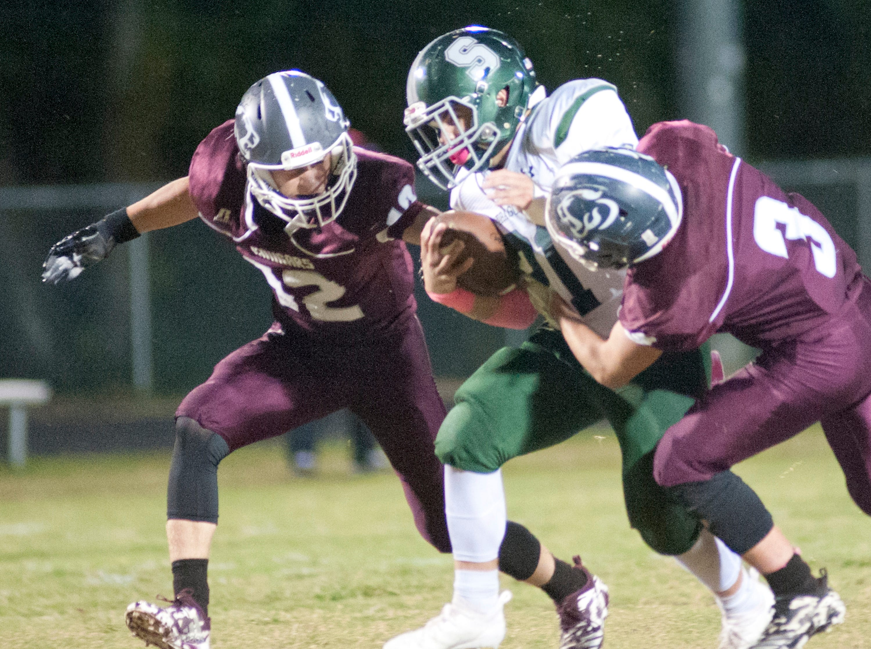 Bullitt Central safety Phillip Hughes, left, and Bullitt Central safety Kylor Close, right, have South Oldham running back Keaton Martin in their gasp. Oct. 12, 2018