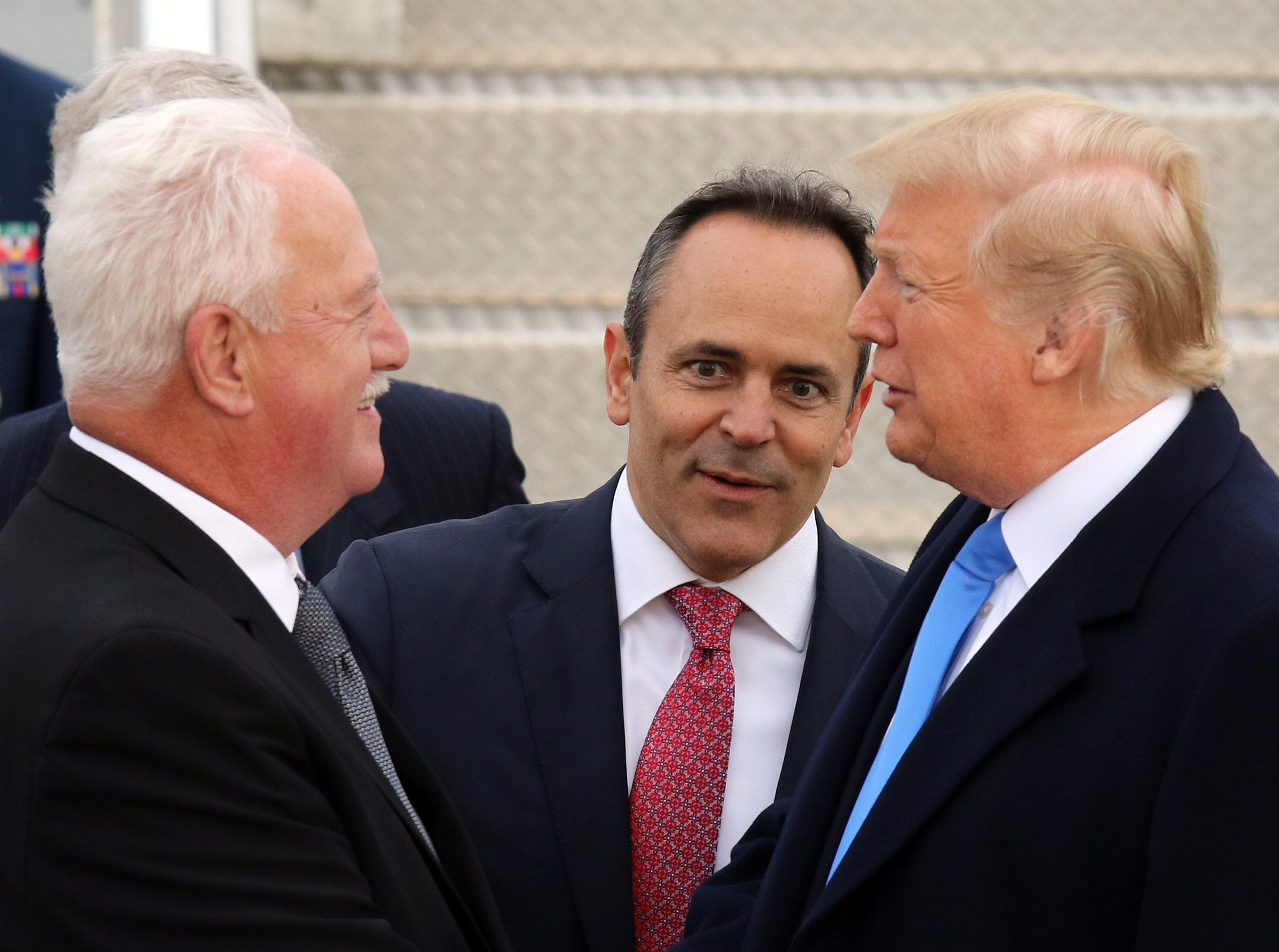 Gov. Bevin, middle, looks on as President Trump, right, greets an individual near Air Force One at Bluegrass Airport in Lexington, Oct. 13, 2018.